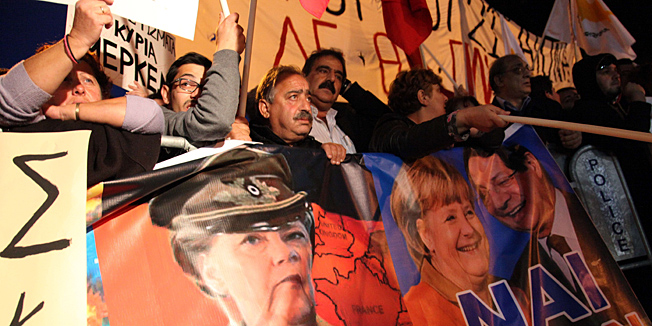 "Cypriot protestors wave banners picturing German Chancellor Angela Merkel (C) and Cypriot President Nicos Anastasiades (R) during a demonstration against an EU bailout deal outside the parliament in the capital, Nicosia, on March 19, 2013. The speaker of the Cypriot parliament urged MPs to say ""no to blackmail"" in a vote on a eurozone bailout aimed at saving the Mediterranean island from bankruptcy. AFP PHOTO/BARBARA LABORDE"