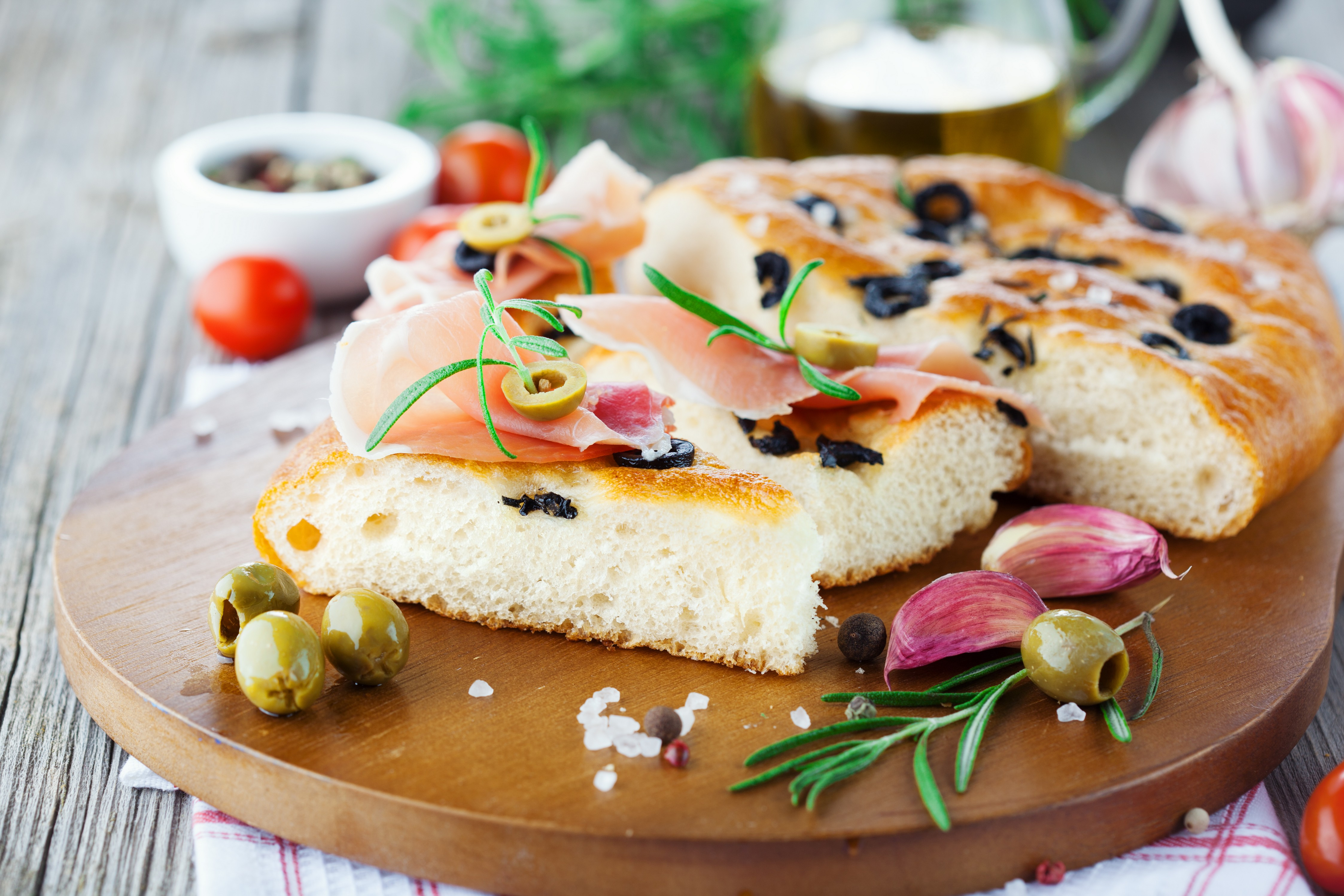 Freshly baked traditional Italian focaccia bread with rosemary, prosciutto ham and black olives on old wooden background, selective focus