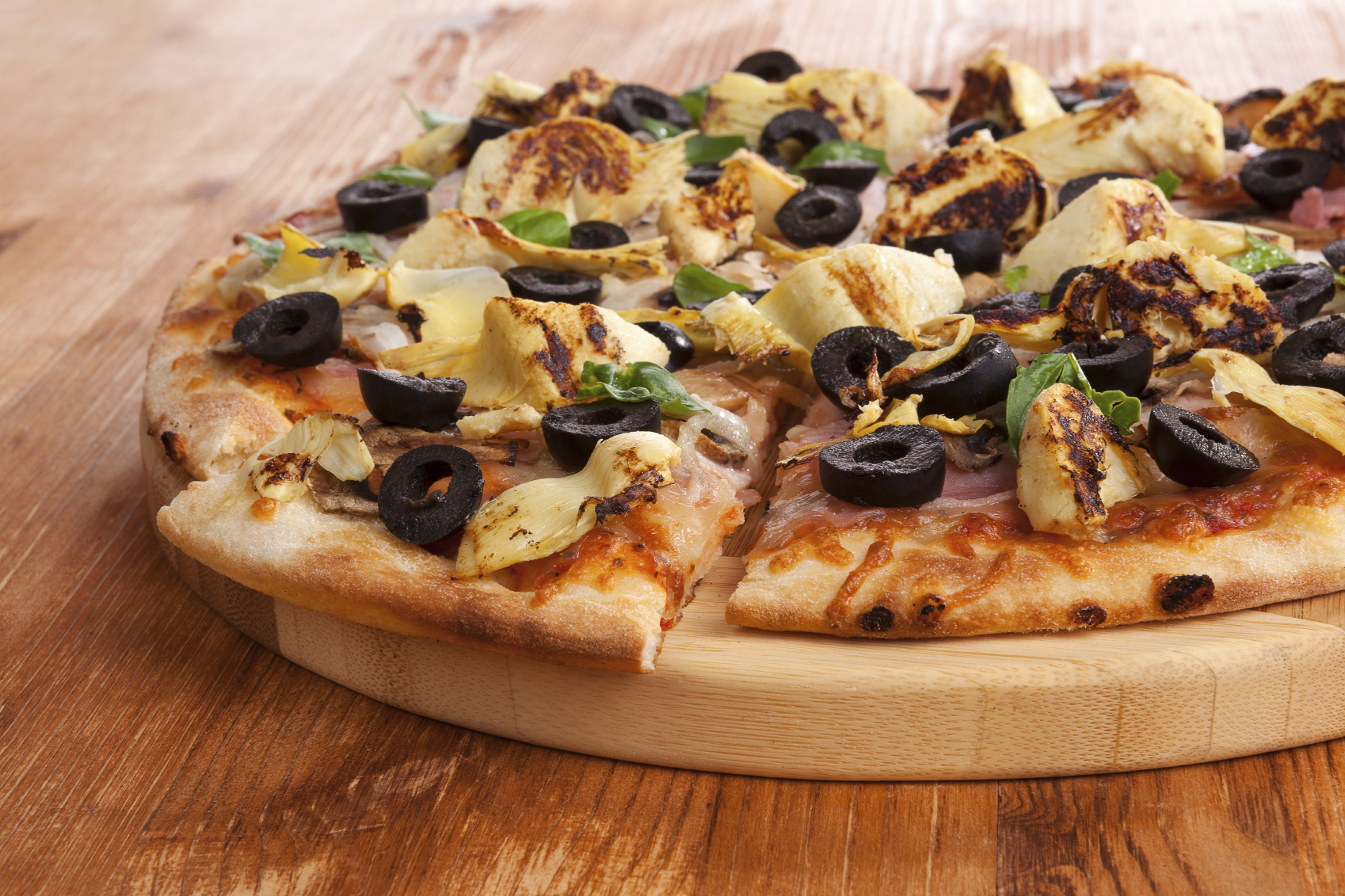 Pizza detail on wooden background. Italian cuisine, pizza with black olives, artichokes and ham. Culinary eating.
