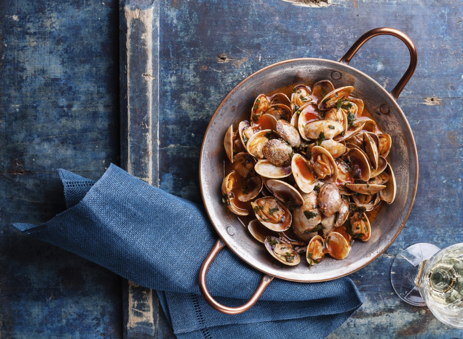 Shells vongole with parsley and tomato sauce and wine on blue background
