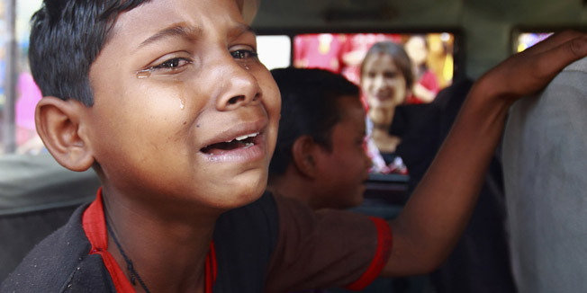A boy cries as he sits inside a vehicle after being rescued from a sari embroidery factory in Kathmandu, a day after the World Day against Child Labour, June 13, 2013. A total of 39 children who were rescued from the factory were taken to a transit home by Central Child Welfare Board and will be handed over to their respective families. Over 80 embroidery factories are located in the Kathmandu Valley, where more than 500 children, mostly below 14 years of age, are employed, according to a researcher at Child Development Society (CDS).  REUTERS/Navesh Chitrakar (NEPAL - Tags: SOCIETY BUSINESS TEXTILE POLITICS EMPLOYMENT) - RTX10LXU