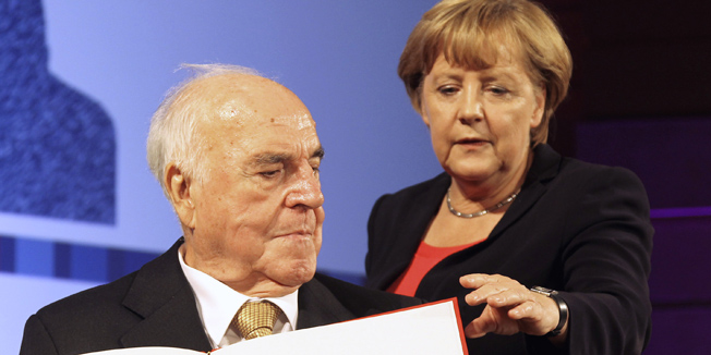 Germany's former Chancellor Helmut Kohl and German Chancellor Angela Merkel attend a stamp unveiling ceremony during a reception in Berlin, September 27, 2012.  REUTERS/Wolfgang Kumm/Pool (GERMANY - Tags: POLITICS) - RTR38IB4