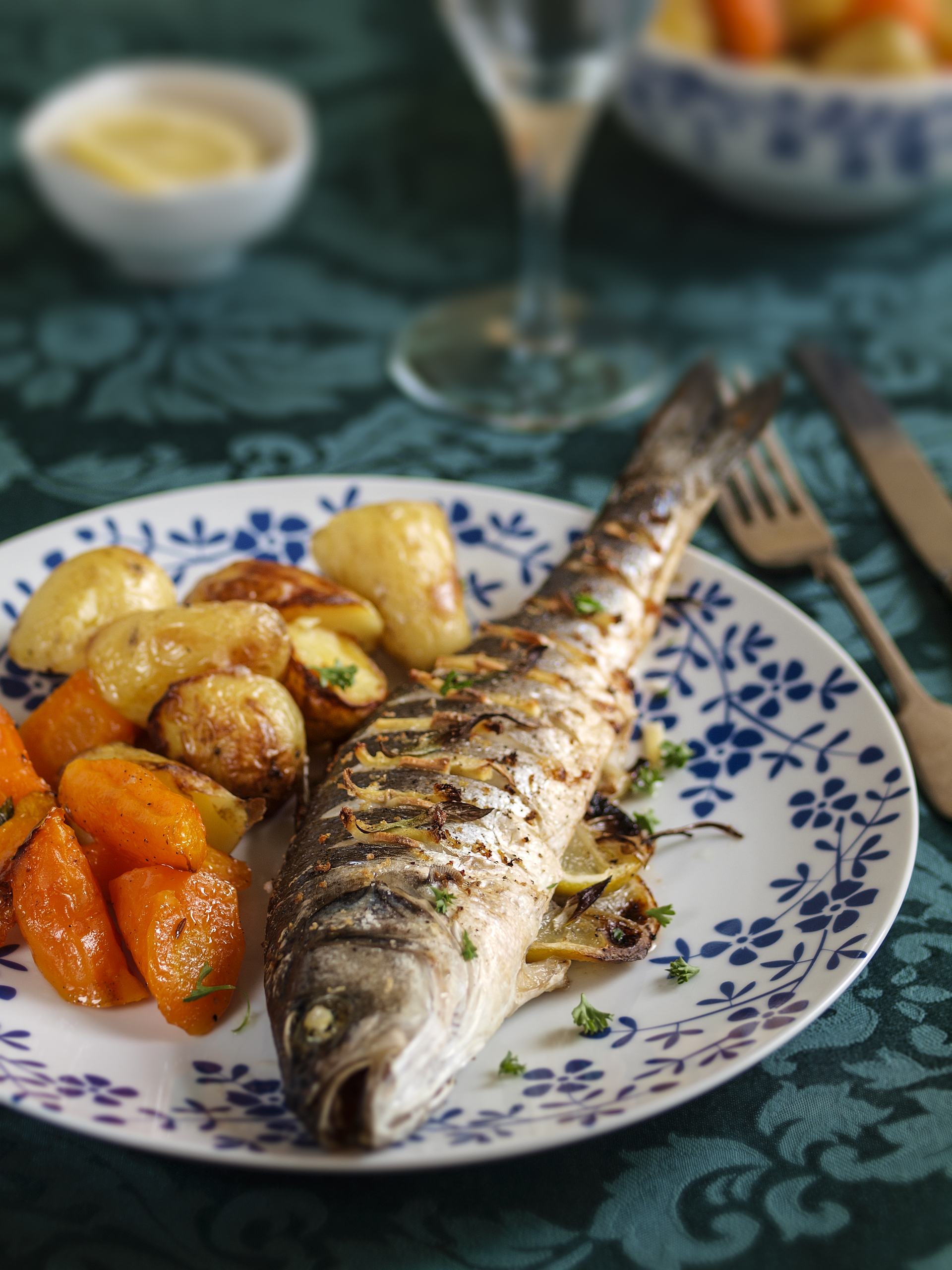 Oriental style baked whole sea bass,baked with ginger,garlic,spring onion,add a bit of soy sauce and coriander,service with roasted potatoes and carrots.