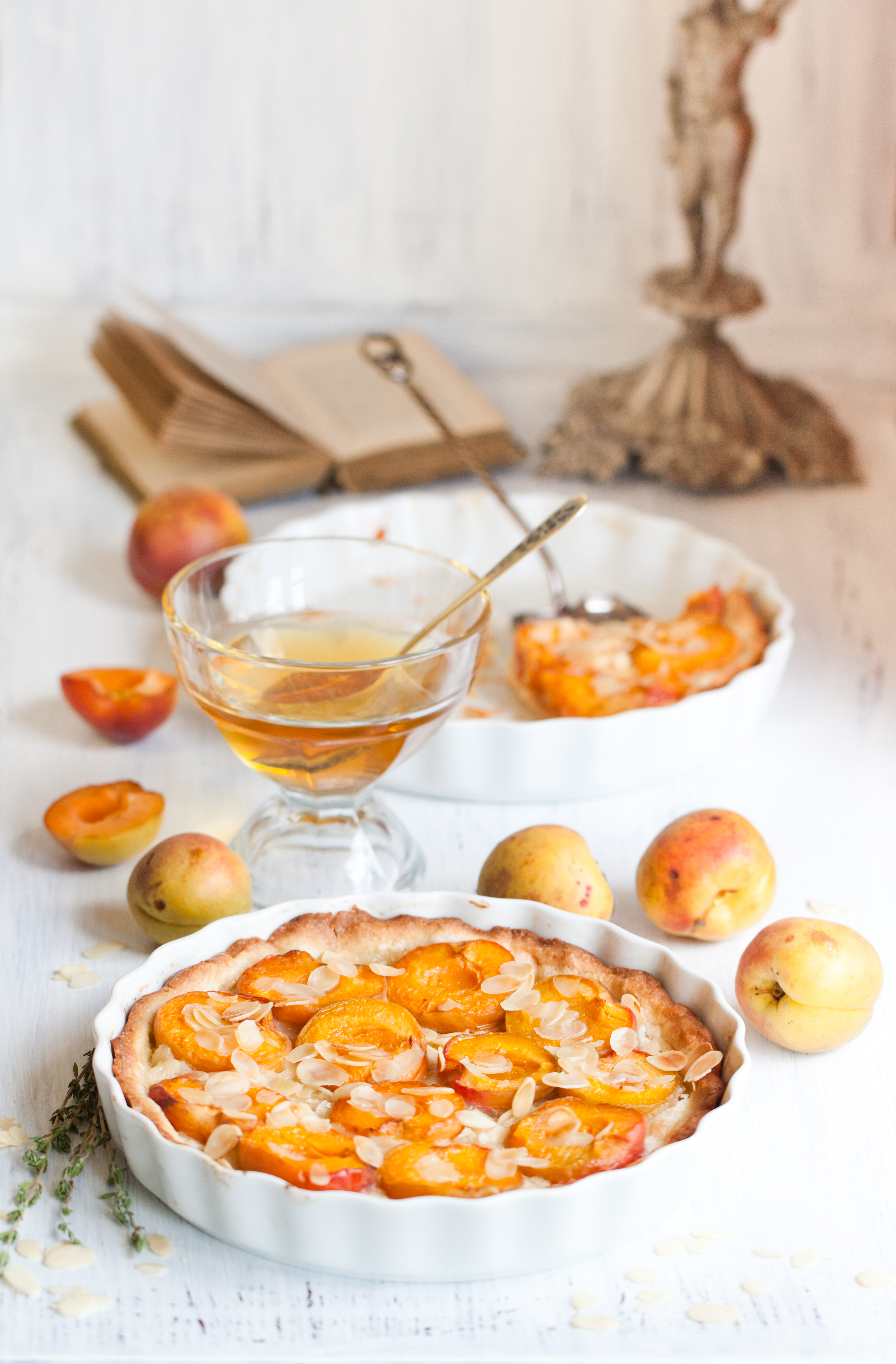 Breakfast with homemade apricot tart with almonds, fresh apricots and honey on white wooden table
