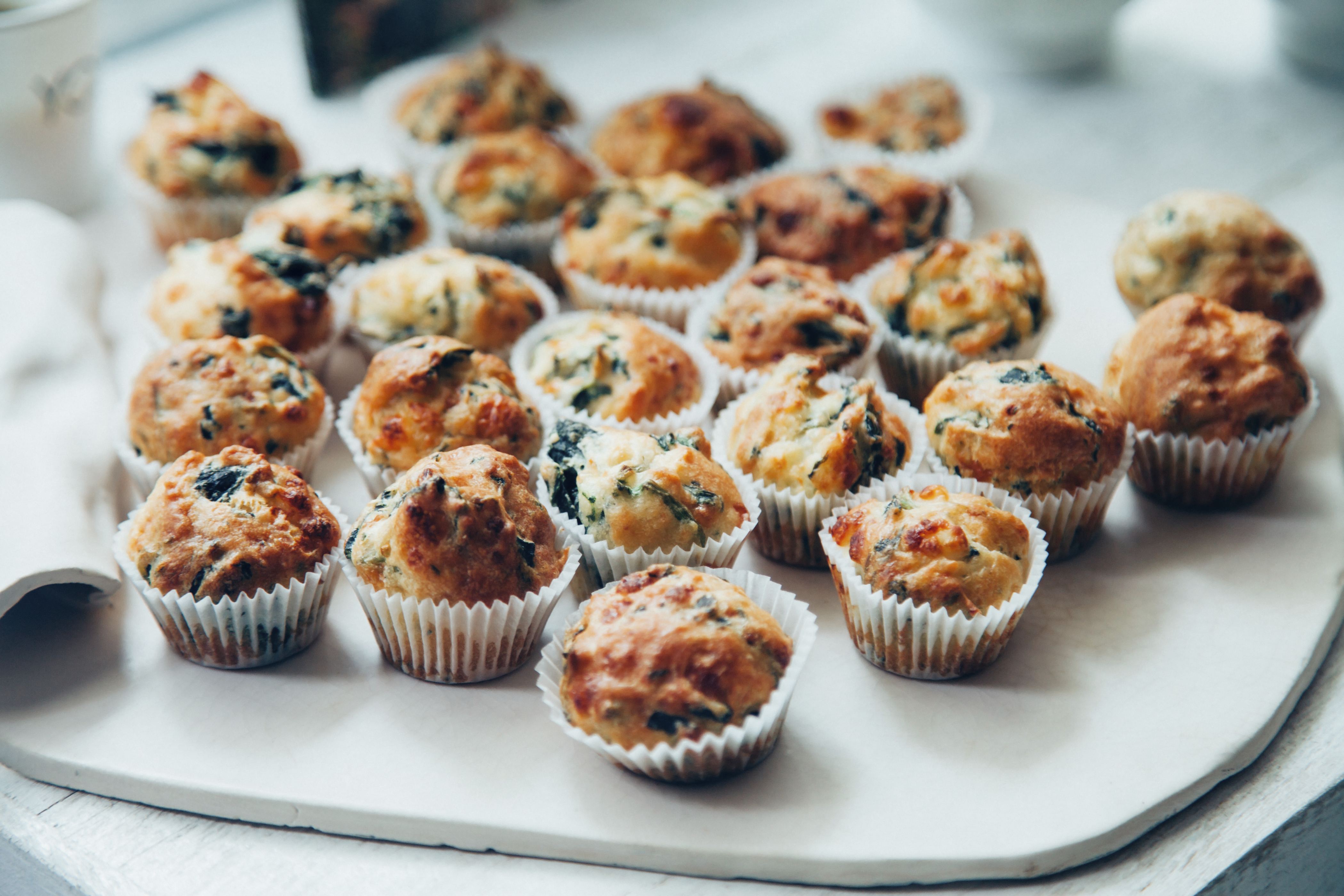 Mini fresh savory vegetable muffins with cheddar cheese, green onions, zucchini and spinach on the white dish