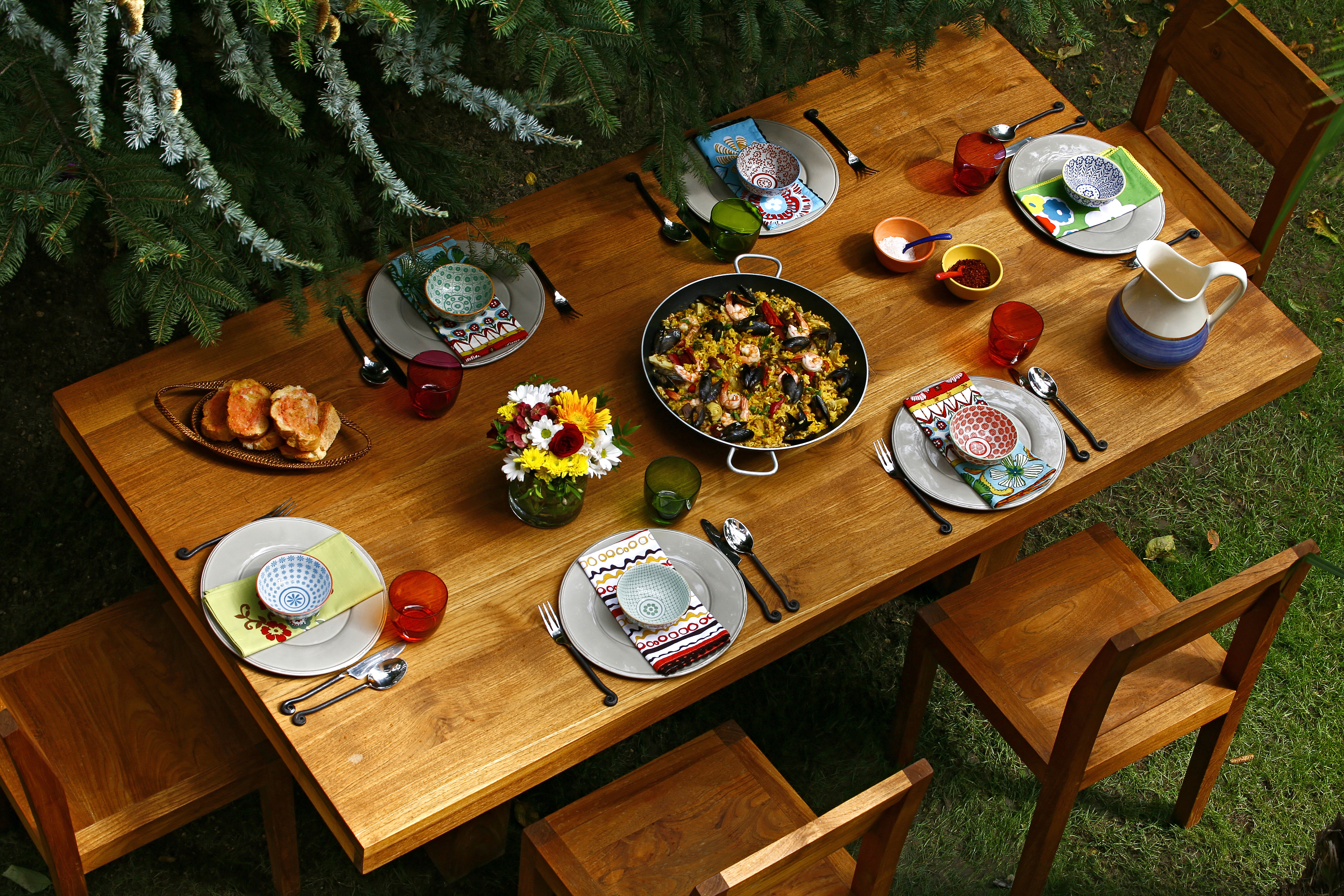 Spanish style dining table with paella and  Spanish style dishes on wooden table in backyard. Overview.