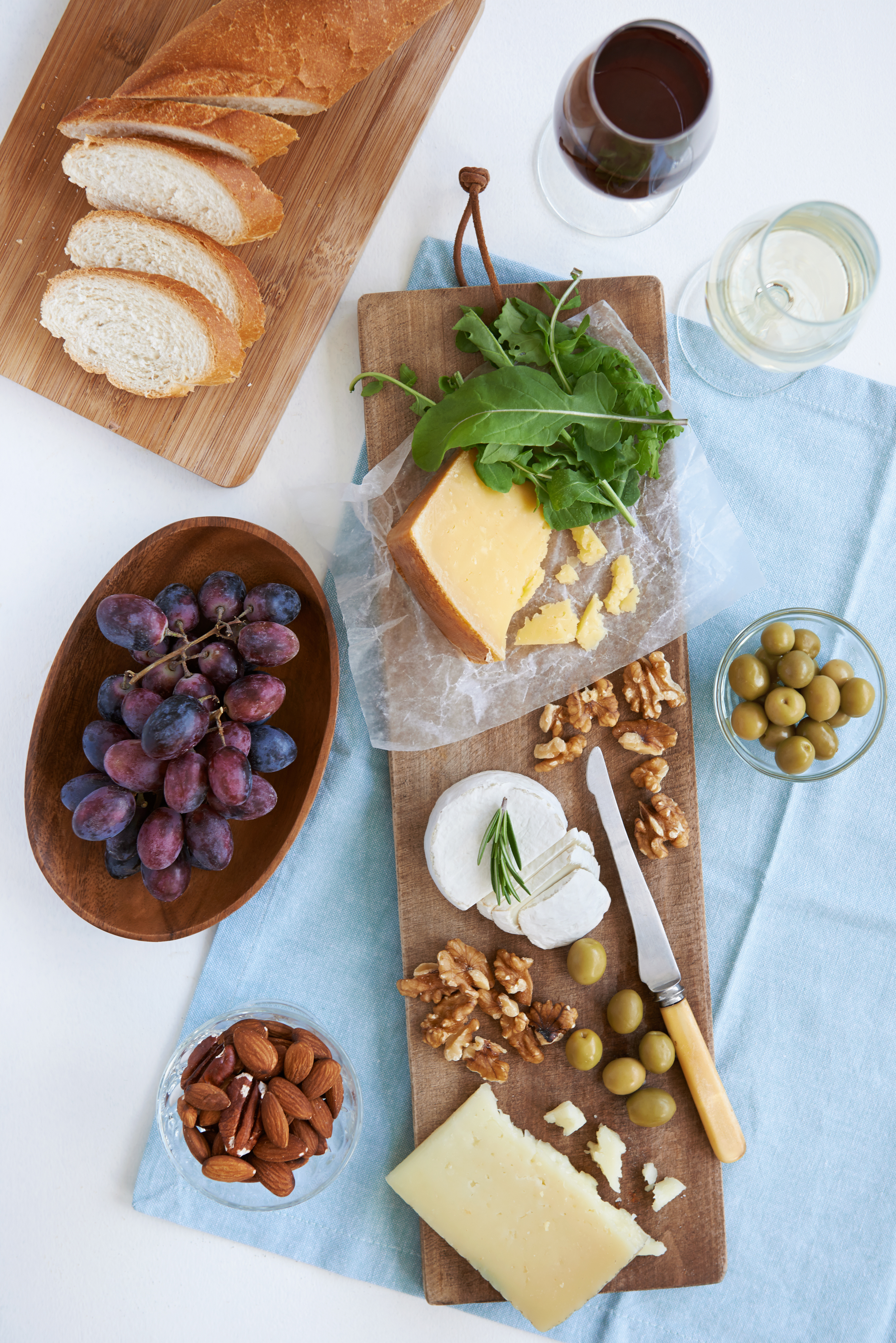 Cheese platter starter appetiser pre dinner snack, assortment of different cheeses, nuts, olives and grapes served with wine