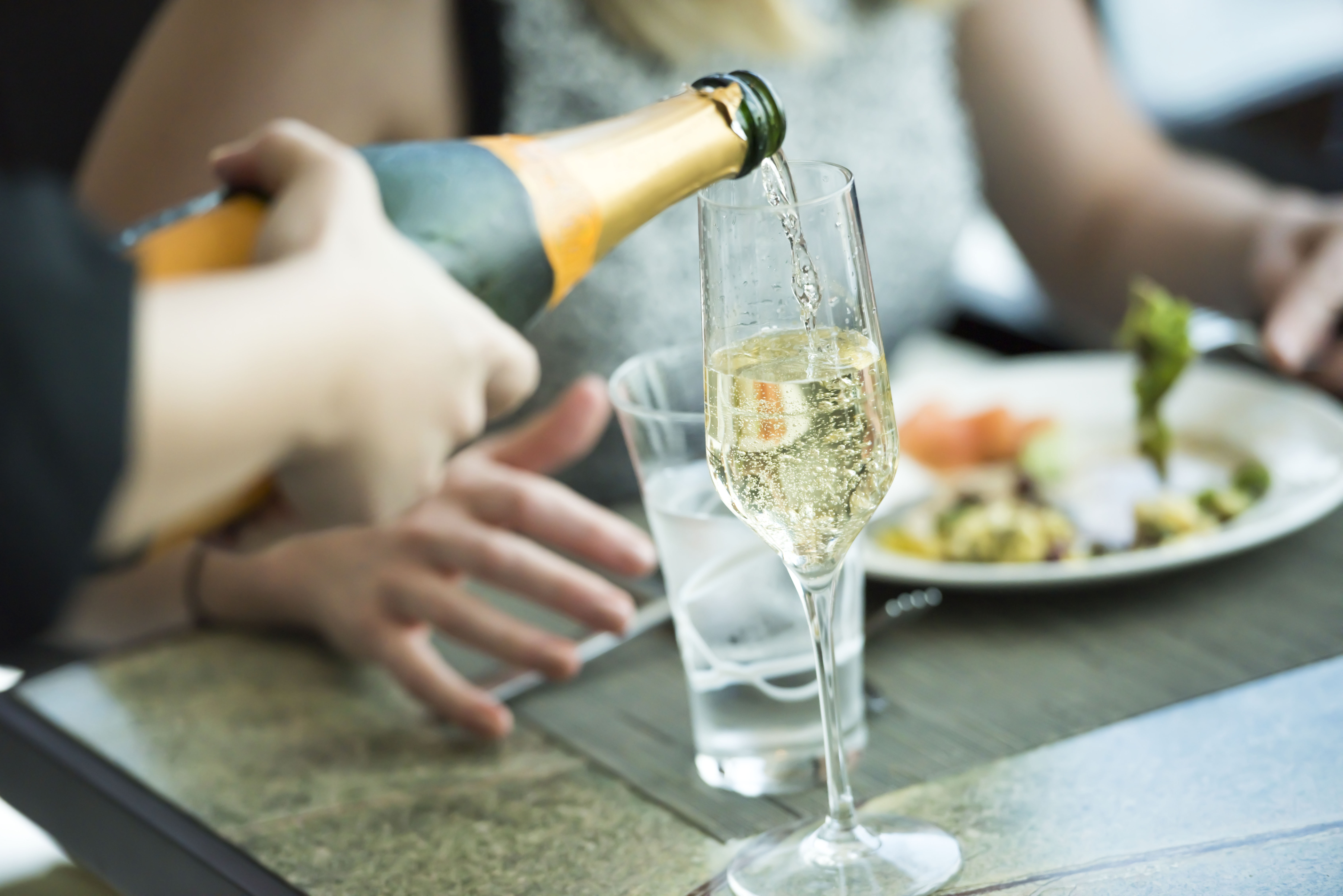 Pouring champagne into the glass, selective focus
