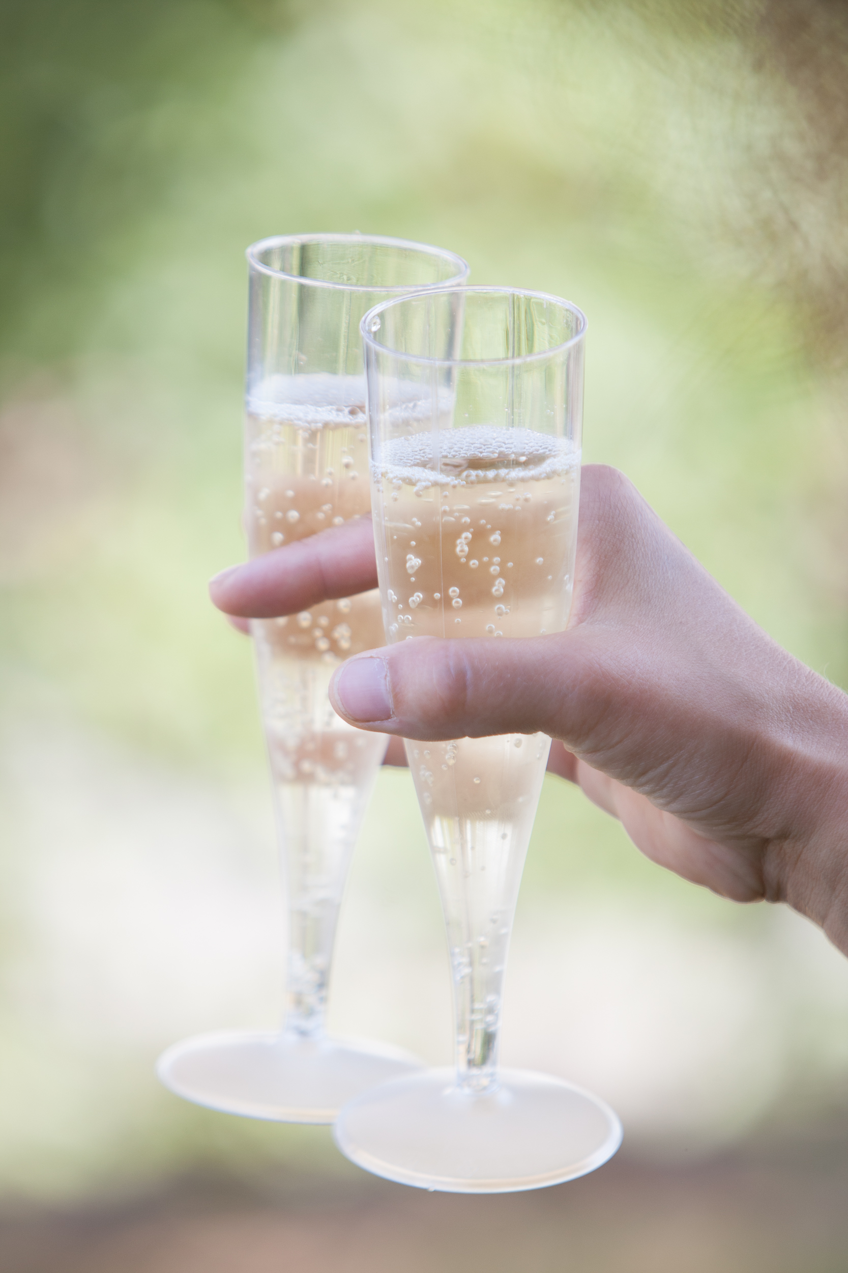 A female hand holding two glasses of champagne, ready to drink and toast