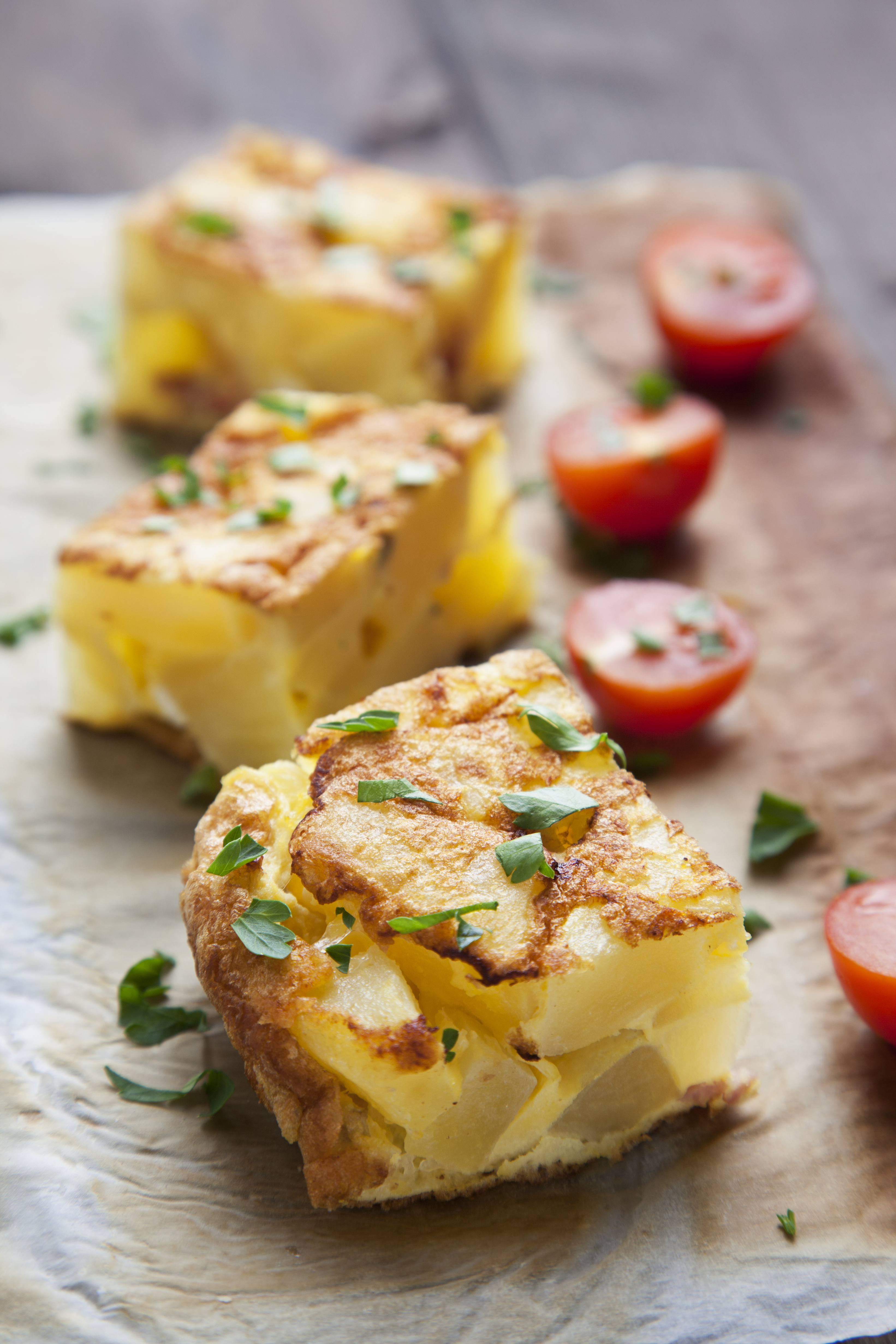 homemade potato frittata with tomatoes and parsley raw on wooden table seen from above