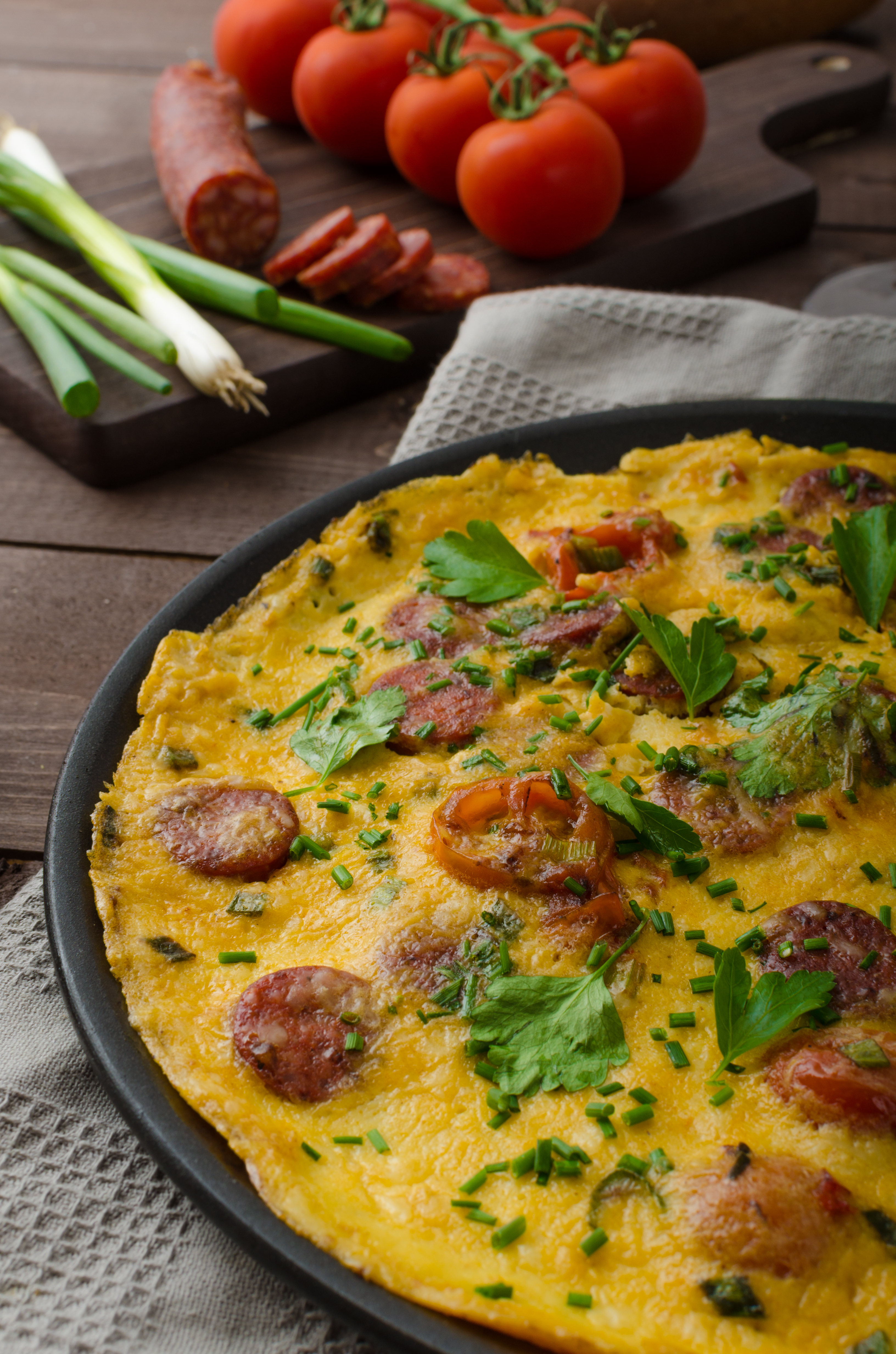 Omelette with chorizo sausage, herbs and tomatoes