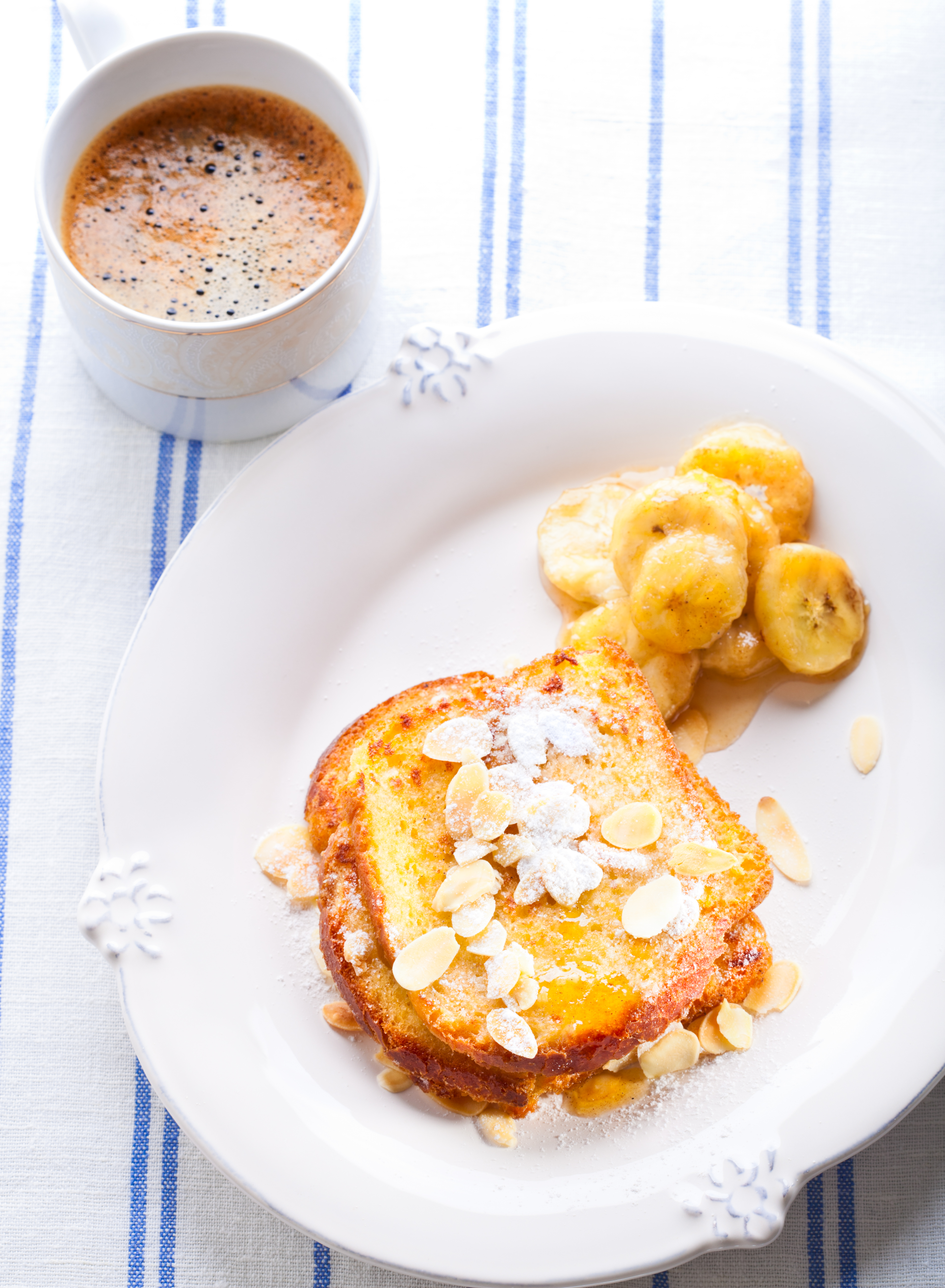 French toast  with bananas in caramel, nuts, powdered sugar and cup of coffee