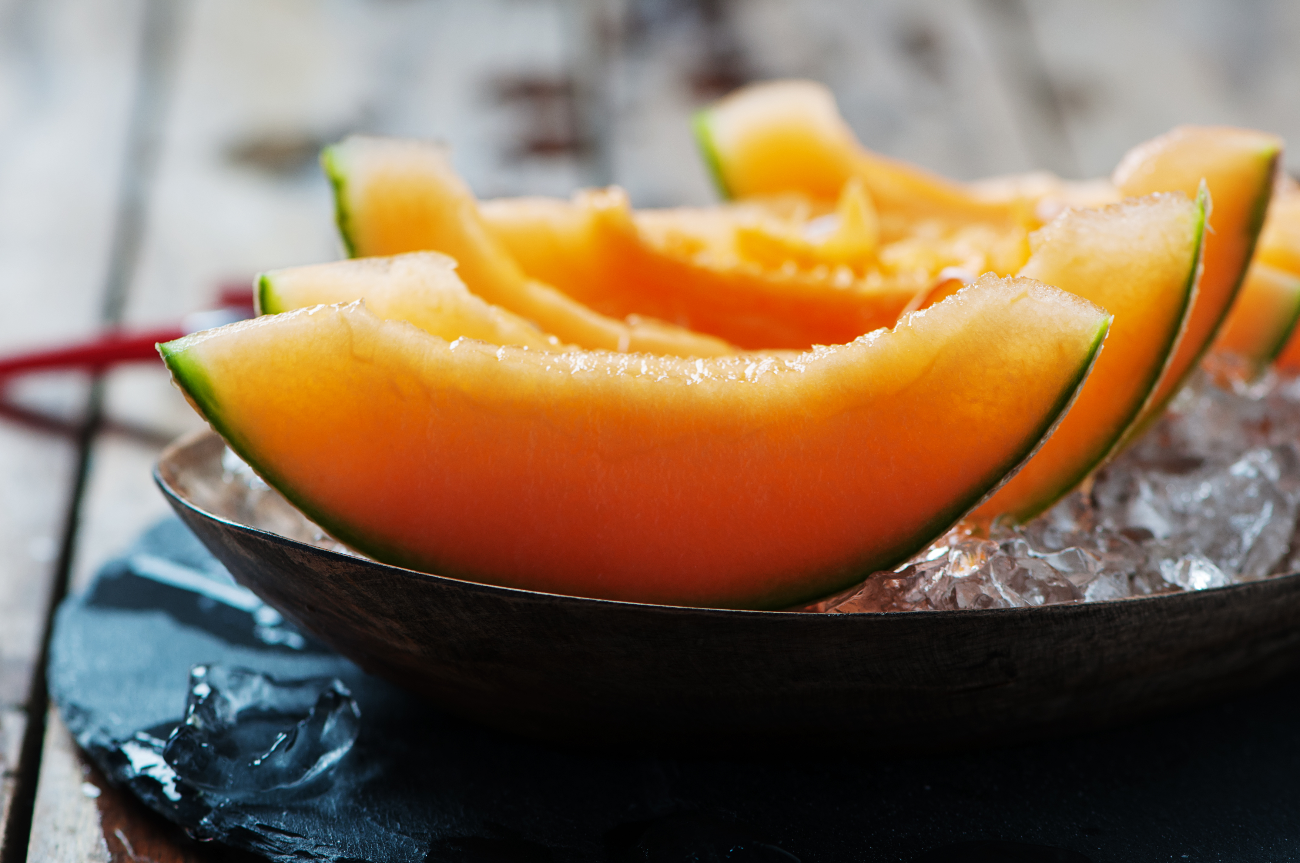 Fresh melon with ice on the wooden table, selective focus