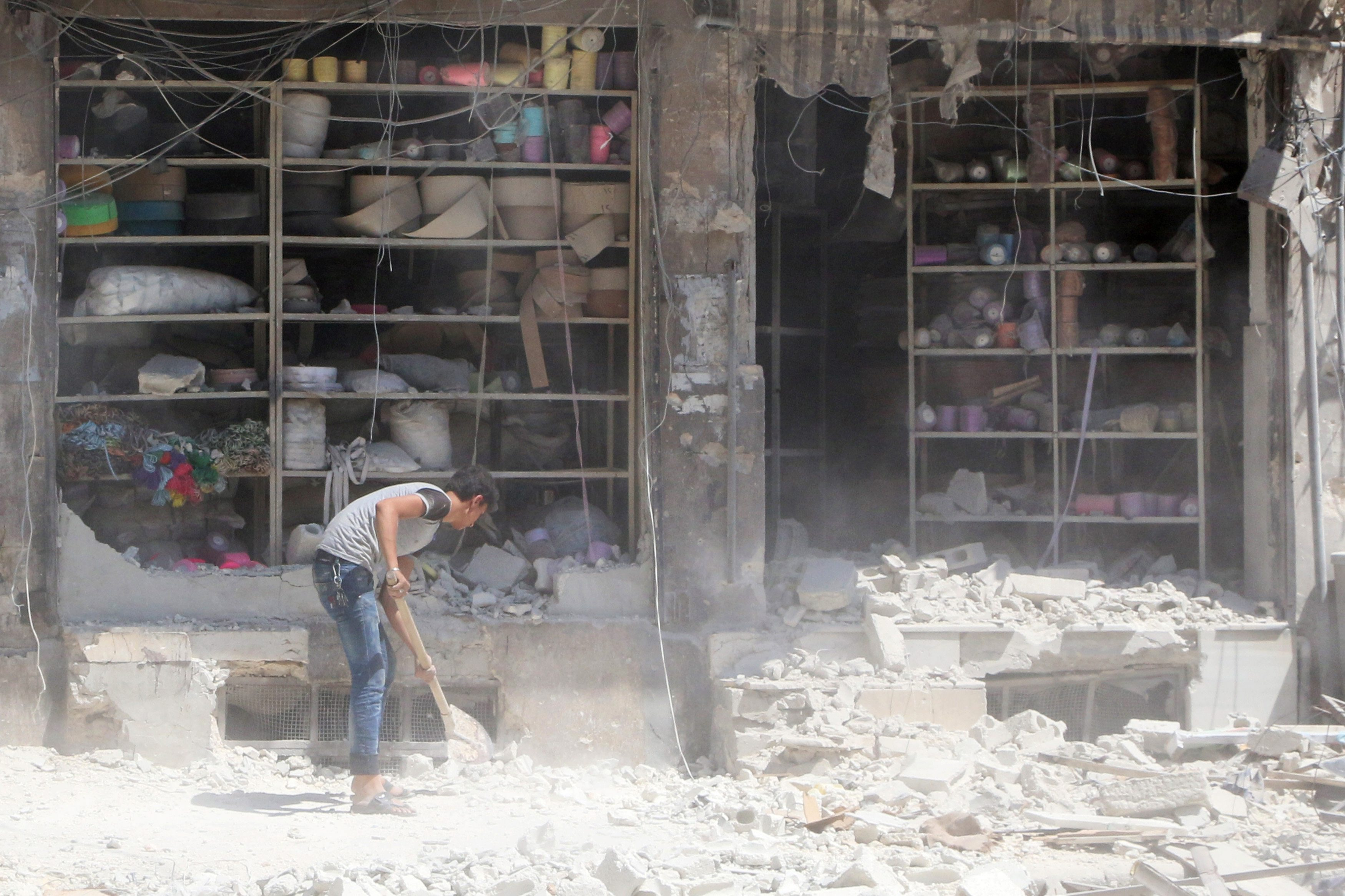 A civilian removes the rubble in front of a damaged shop after an airstrike in the rebel held al-Saleheen neighborhood of Aleppo, Syria August 18, 2016. REUTERS/Abdalrhman Ismail      TPX IMAGES OF THE DAY