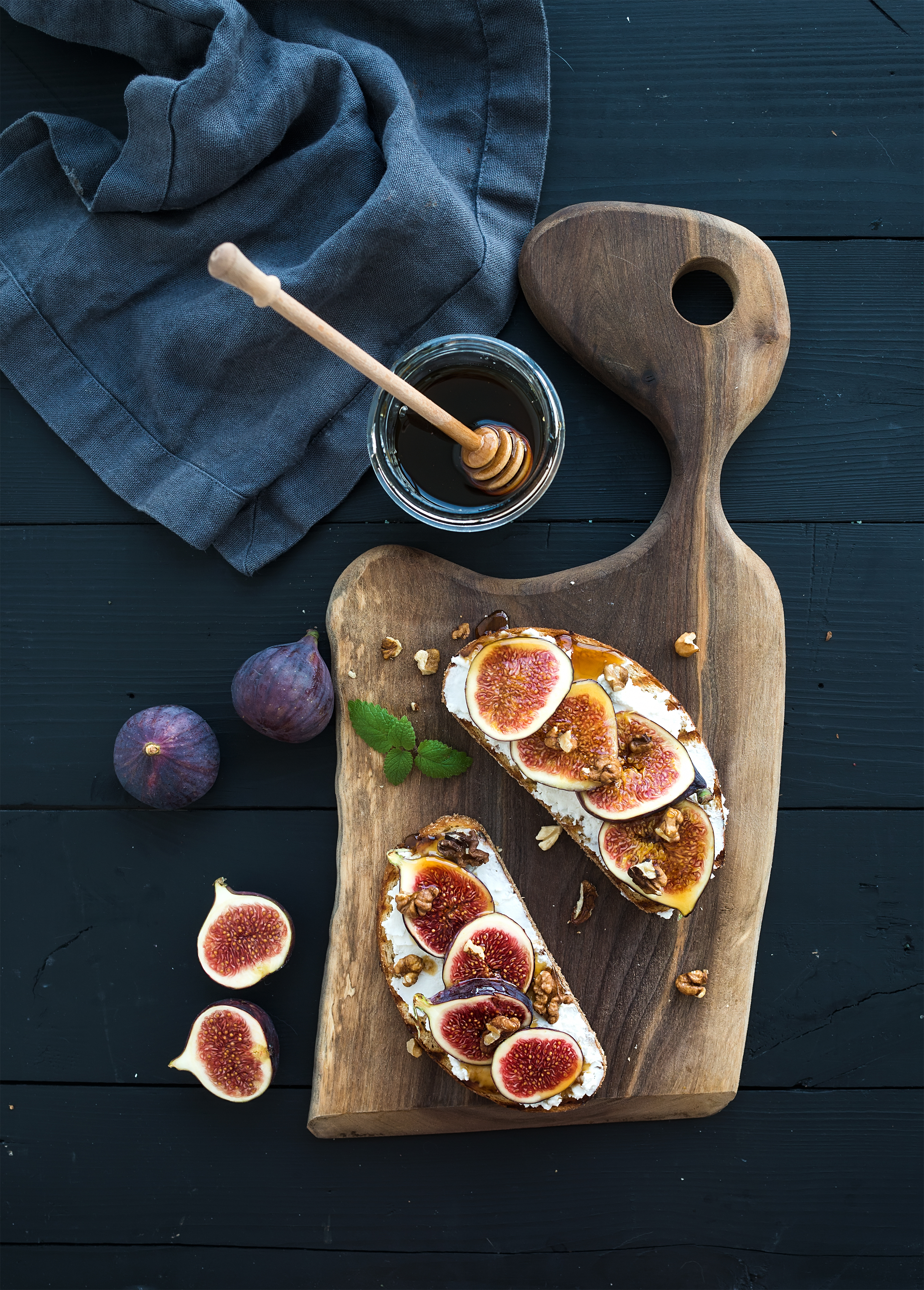 Sandwiches with ricotta, fresh figs, walnuts and honey on rustic wooden board over black backdrop, top view