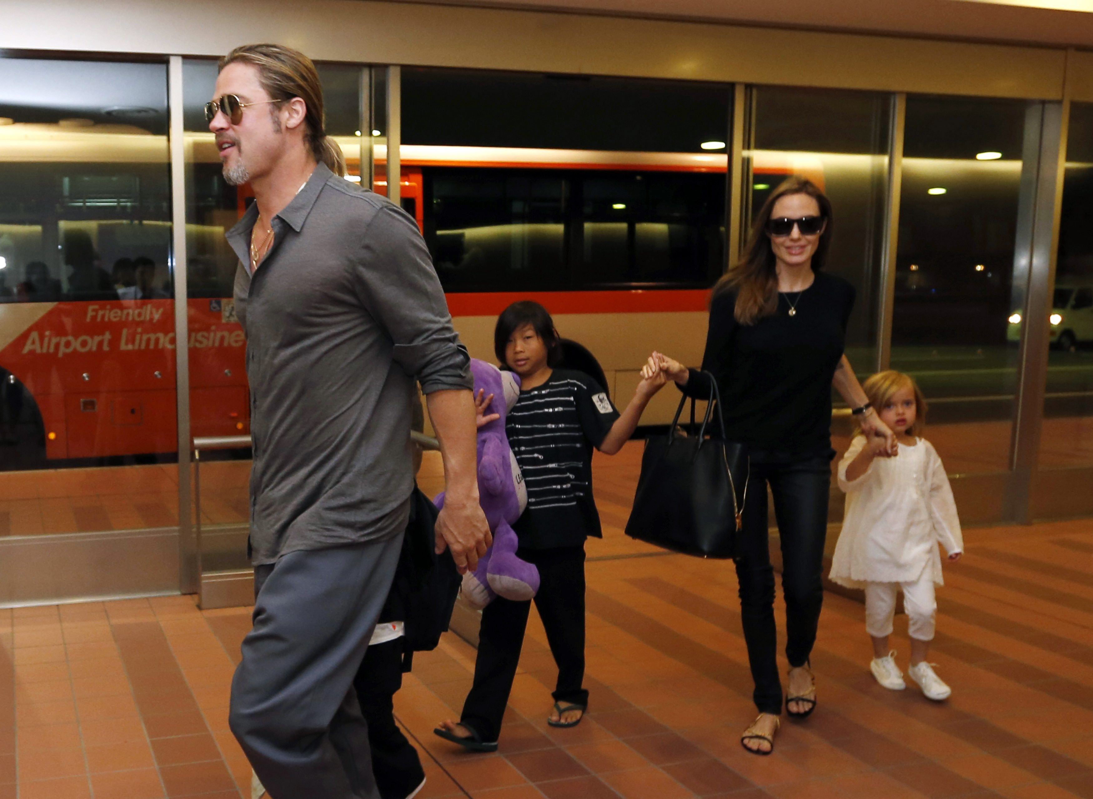 Hollywood actors Brad Pitt (L) and actress Angelina Jolie (2nd R) arrive with their children Knox (beside Pitt), Vivienne (R) and Pax (C) at Haneda international airport in Tokyo, Japan on July 28, 2013.  REUTERS/Issei Kato/File Photo
