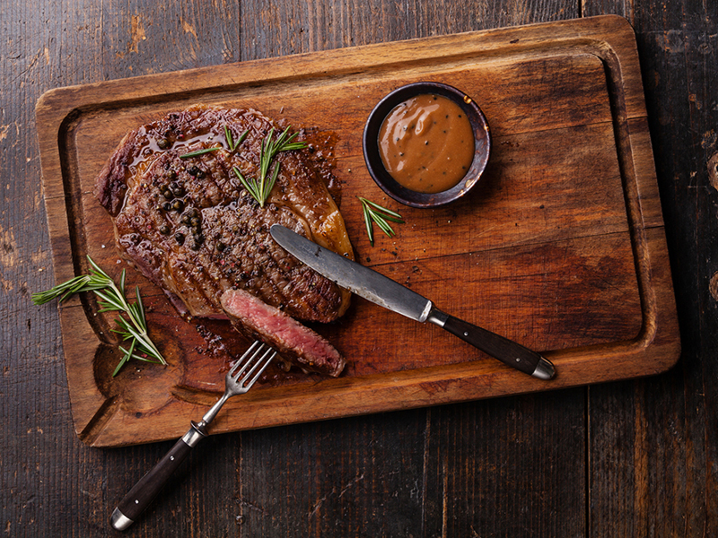 Grilled Black Angus Steak Ribeye and Pepper sauce on meat cutting board on dark wooden background