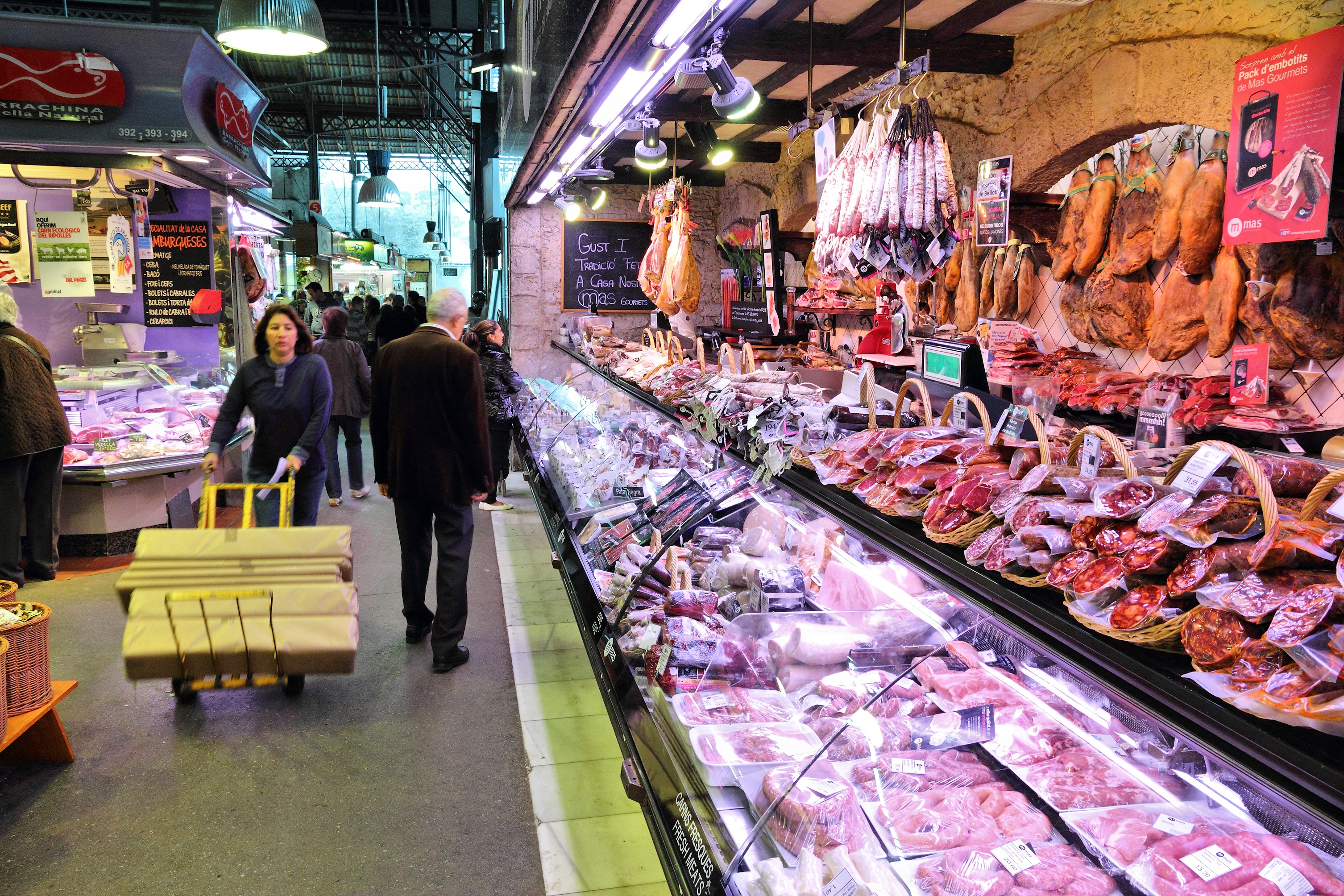Barcelona, Spain - November 6, 2012: People visit meat shop at Boqueria market in Barcelona, Spain. The marketplace in Ciutat Vella district dates back to year 1217.