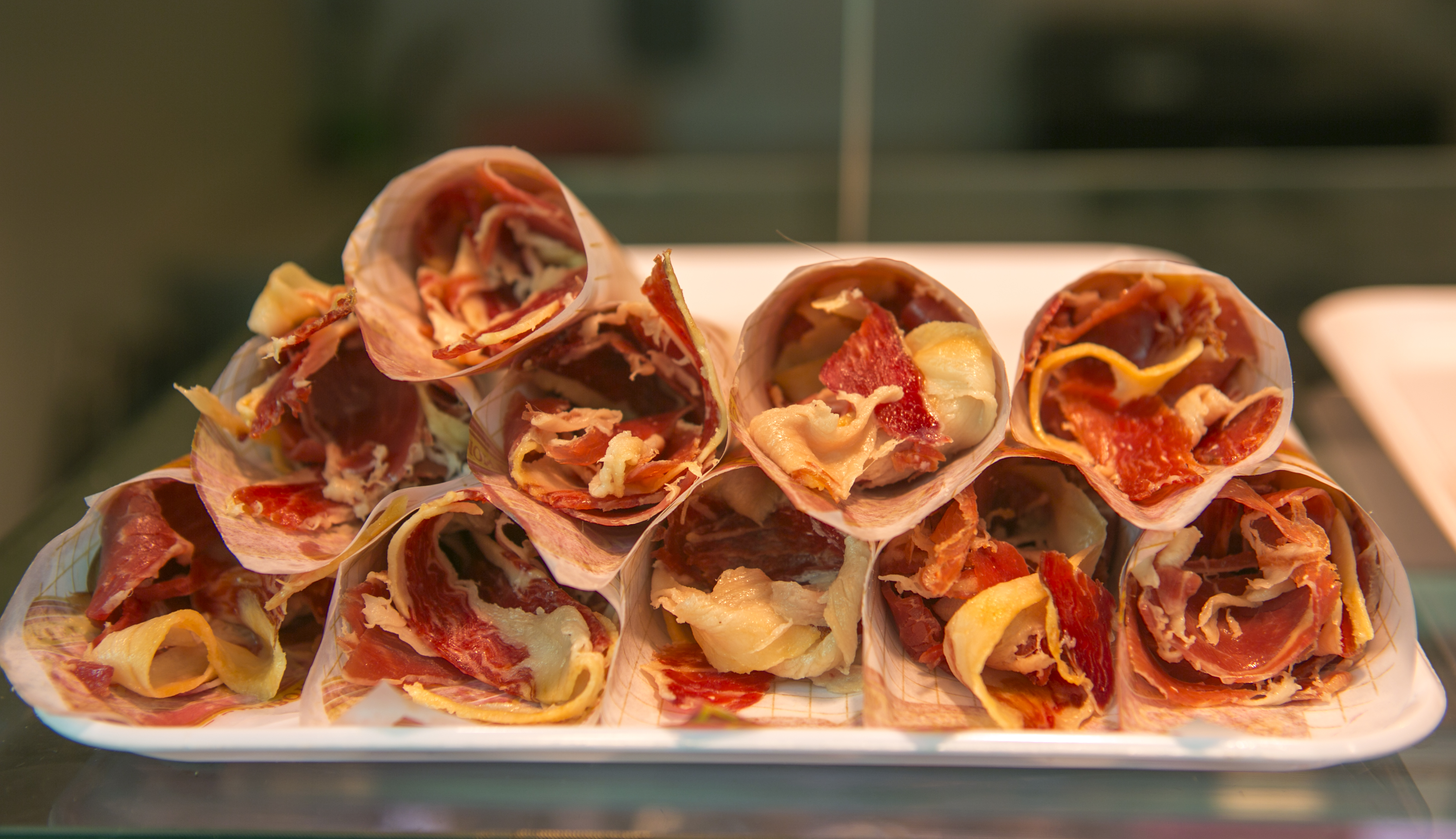 sliced bacons in cone for sale at famous boqueria market of barcelona spain
