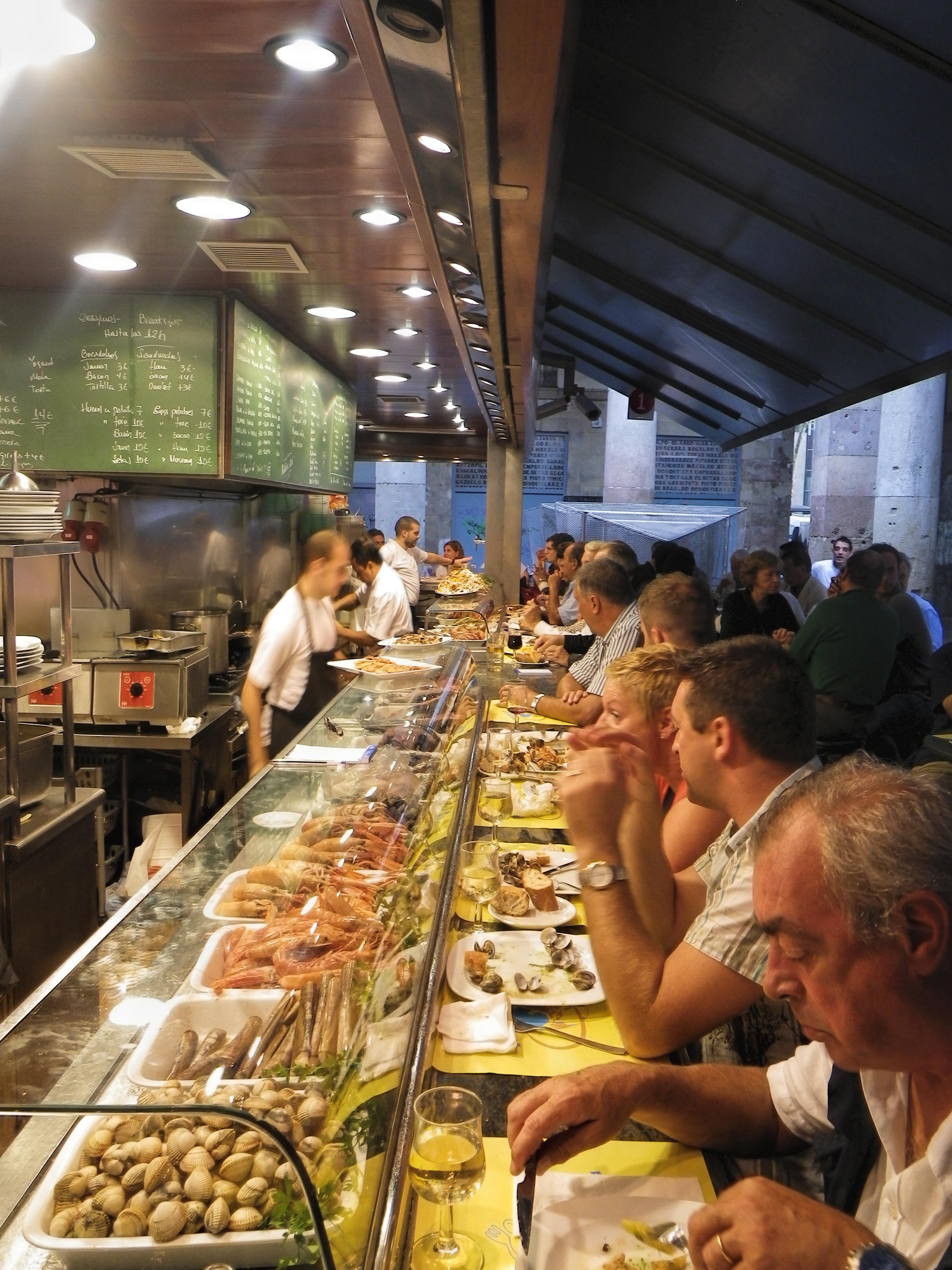 Barcelona, Spain - September 21, 2010: People having lunch in a restaurant in Marcedo de la Boqueria