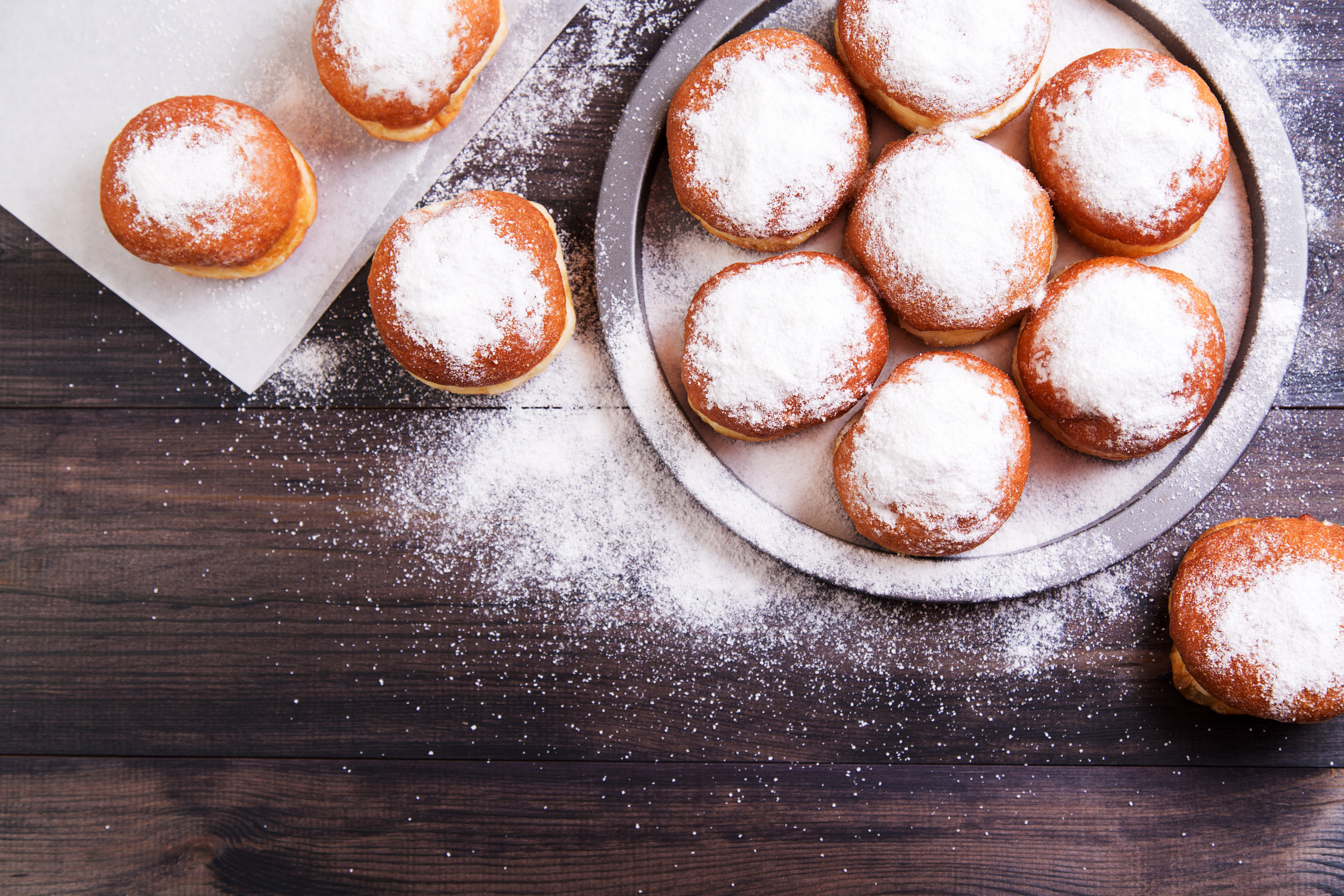 German donuts - berliner with jam and icing sugar in a tray on a wooden background. Top view