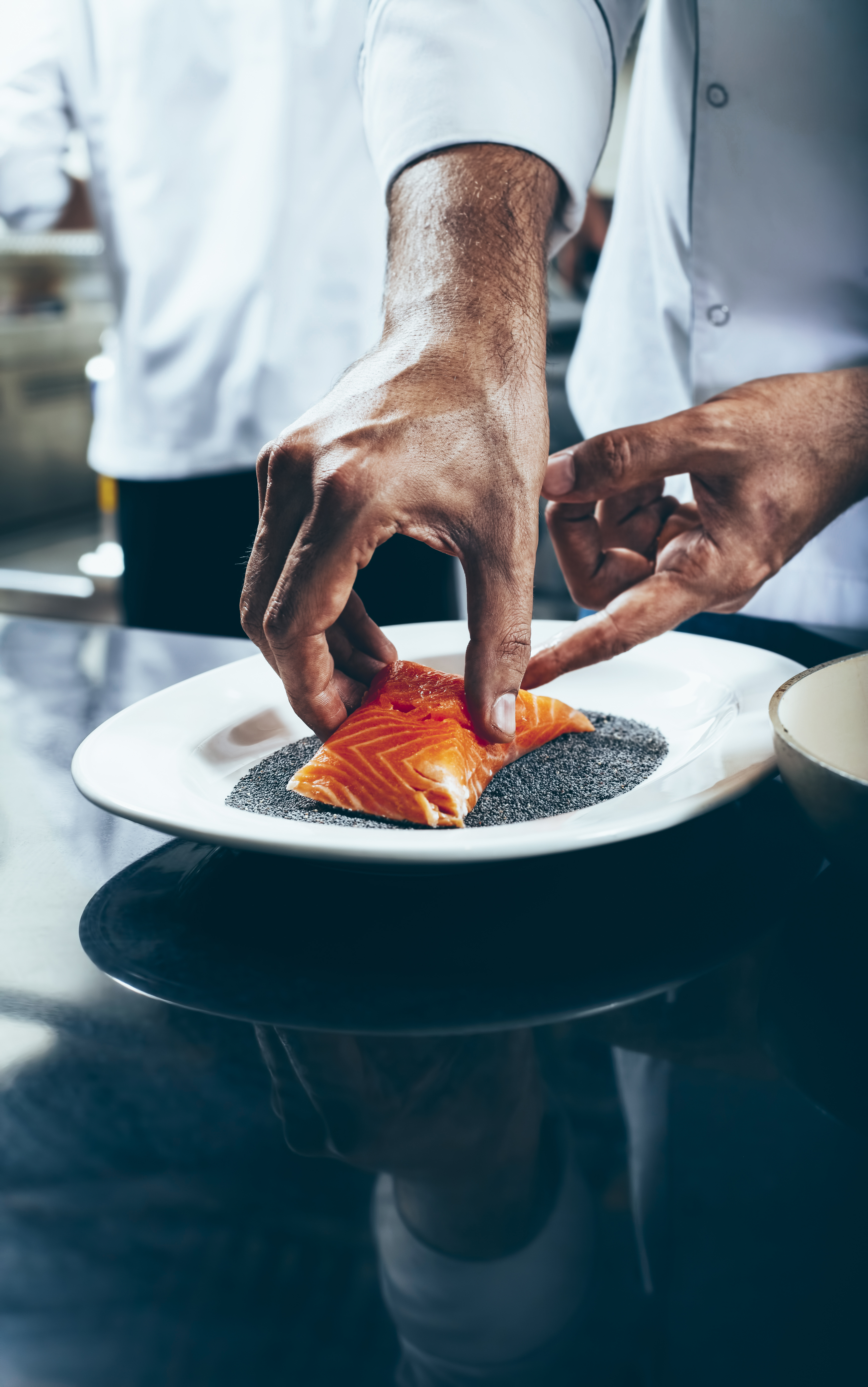 Chef dips salmon fillet on poppy seeds.A caucasian chef holding salmon fillet with two hands.Only hands of chef is visible.There is another chef working at the back.Underside of the image is blank.