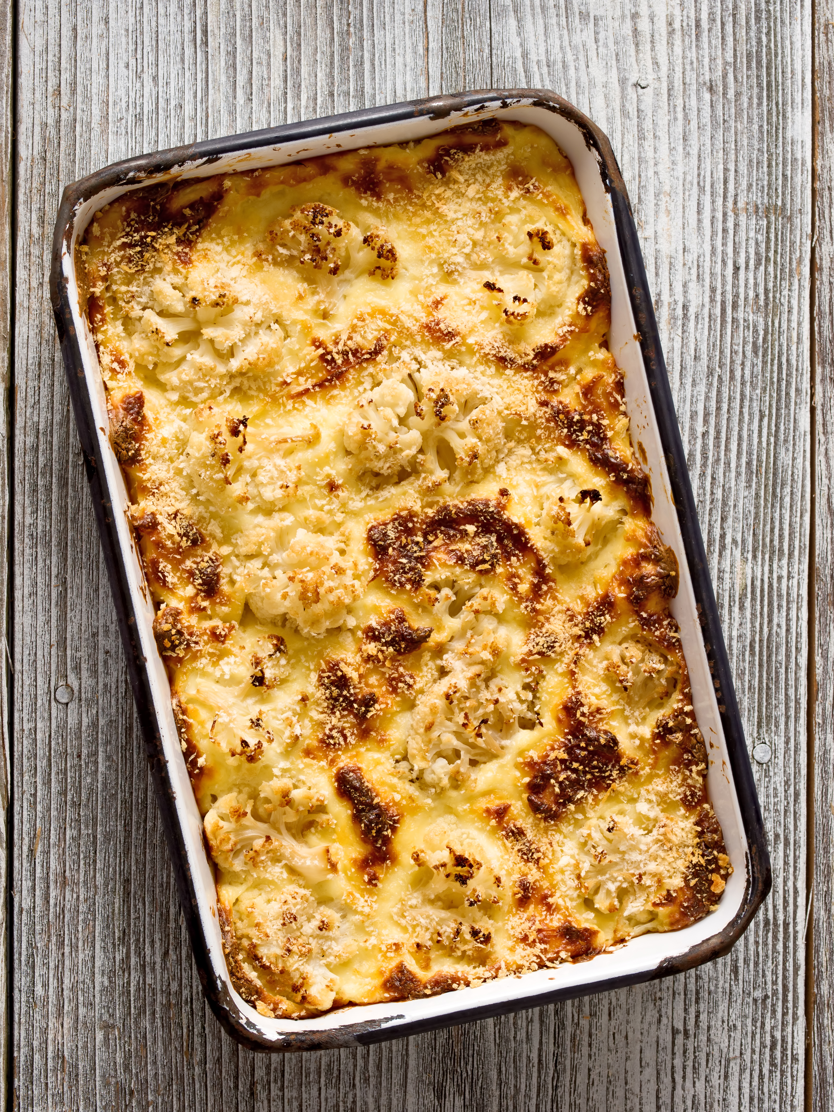 close up of a tray of rustic baked cauliflower cheese
