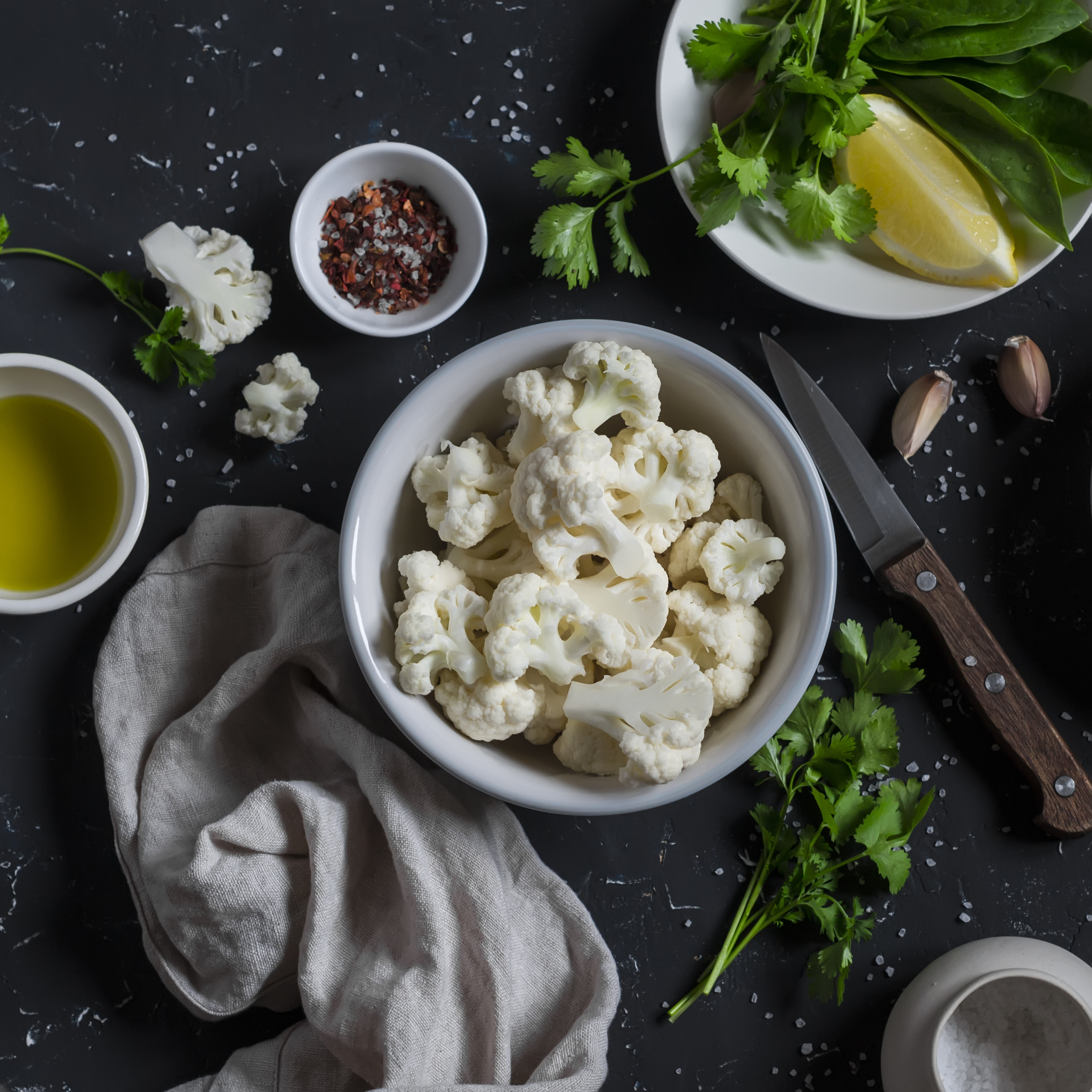 Raw ingredients - cauliflower, olive oil, herbs, lemon and spices on a dark stone background