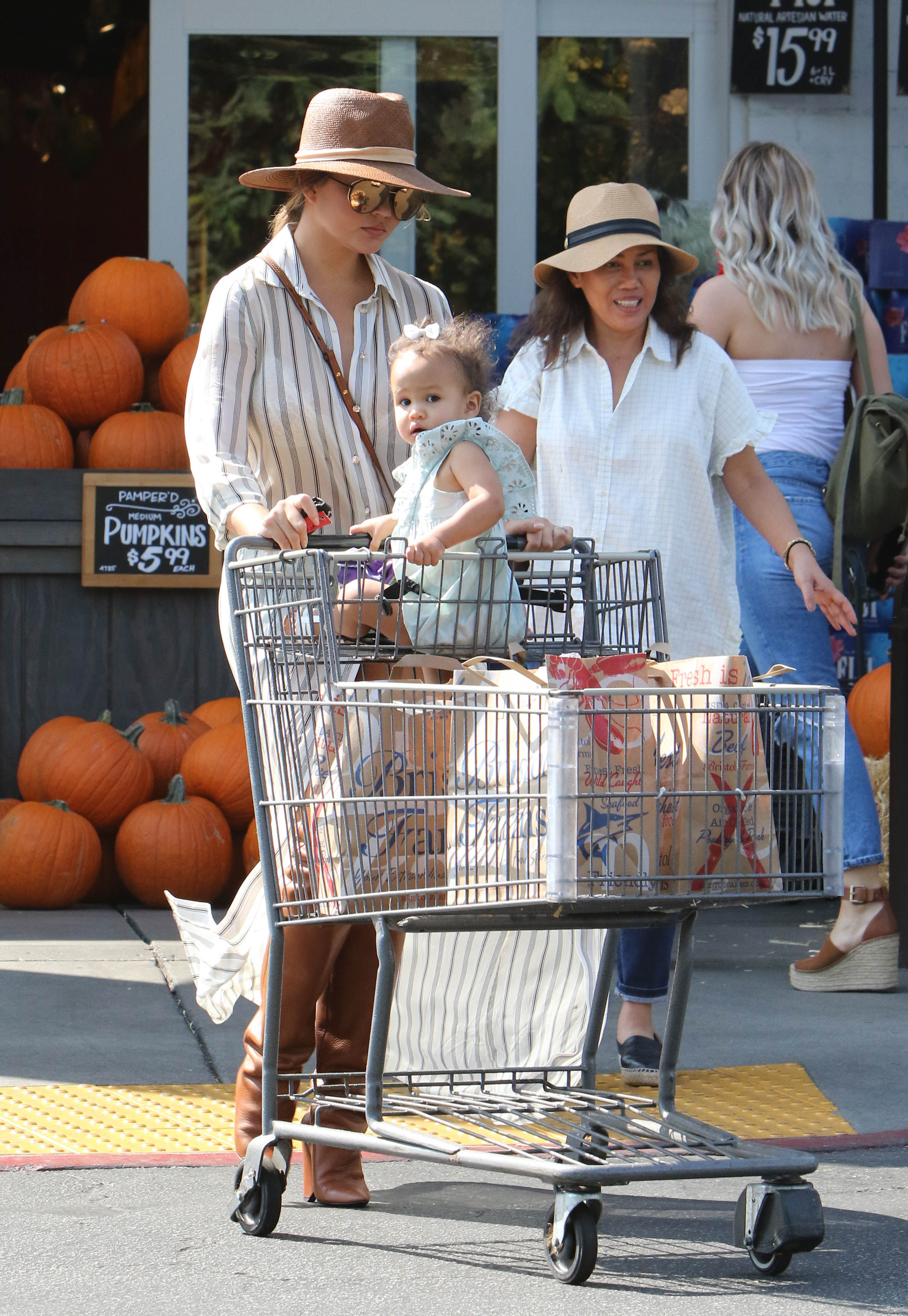 Saturday, September 30, 2017 - Chrissy Teigen takes daughter Luna grocery shopping with her mom Vilailuck at Bristol Farms.  The supermodel showed off three generations of beauty as the family stocked up on fall food.  Teigen carried the latest Chloe Nile bracelet crossbody bag (00) and wore 00 Isabel Marant Lostynn thigh-high leather boots with a flowy button-up worn robe style over her denim cut-offs.  X17online.com