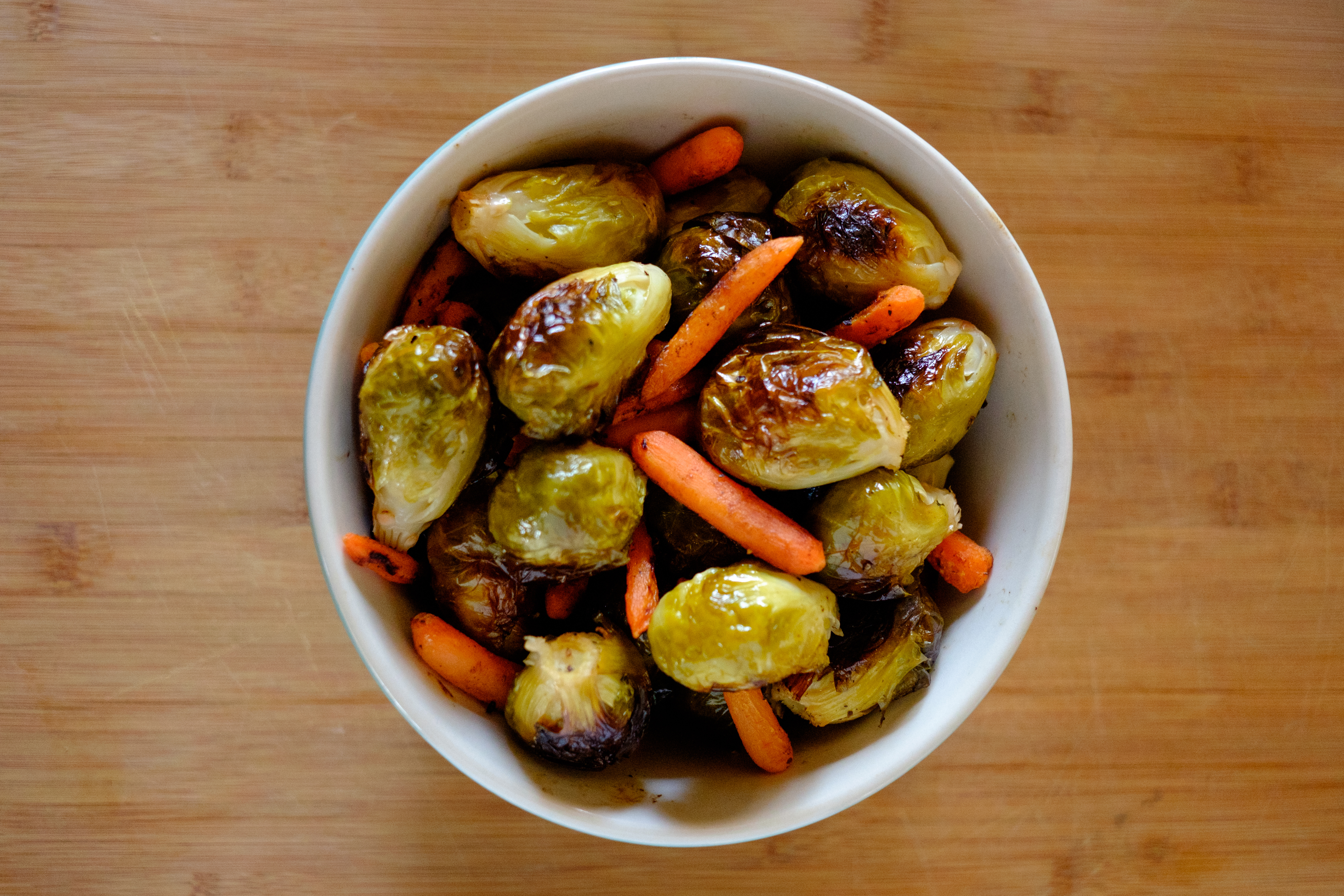 A bowl of delicious and healthy roasted vegetables, including brussel sprouts and carrots.