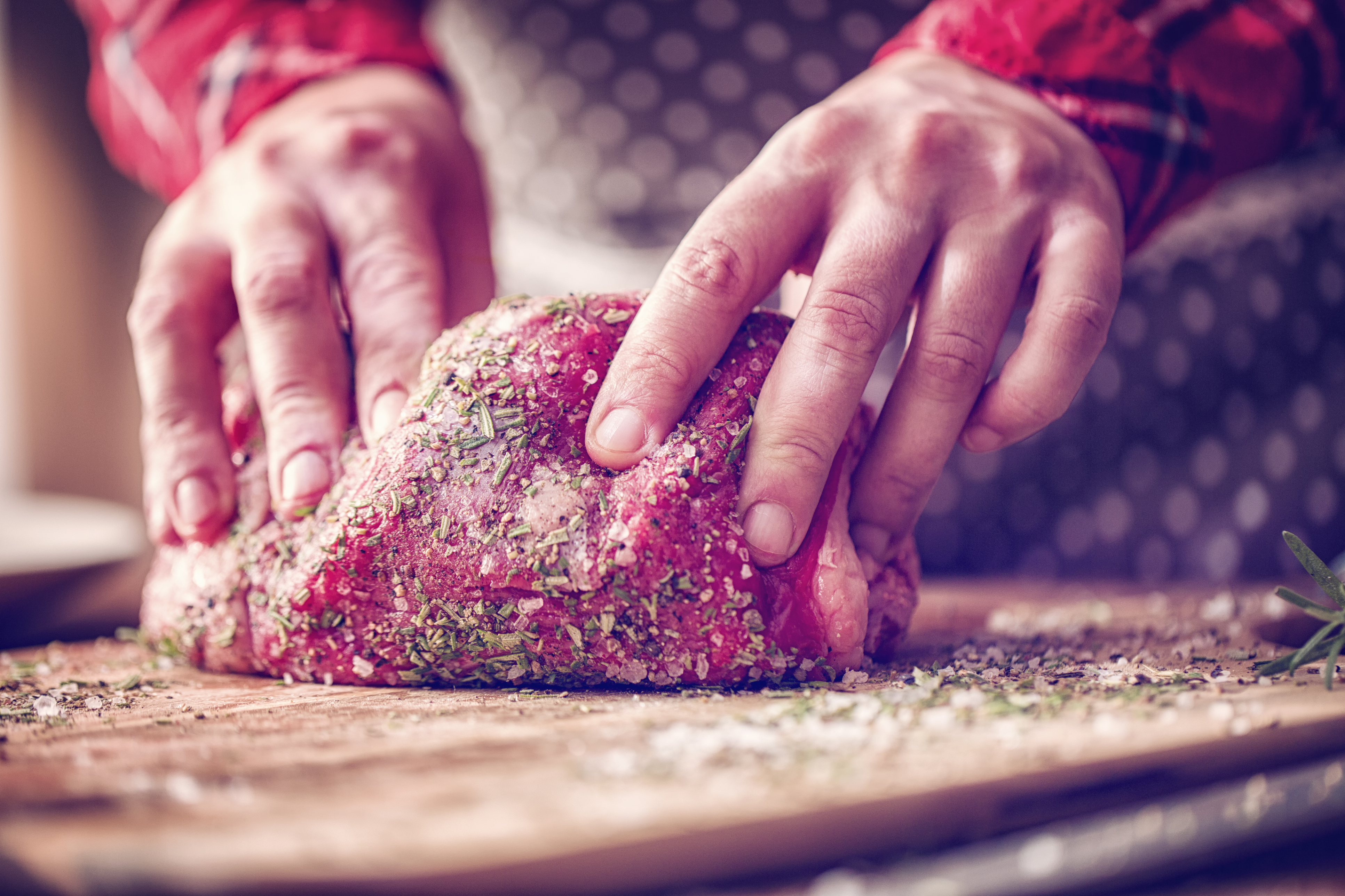 Preparing Roast Beef for lunch by rolling it into fresh herbs and spices on a wooden board.