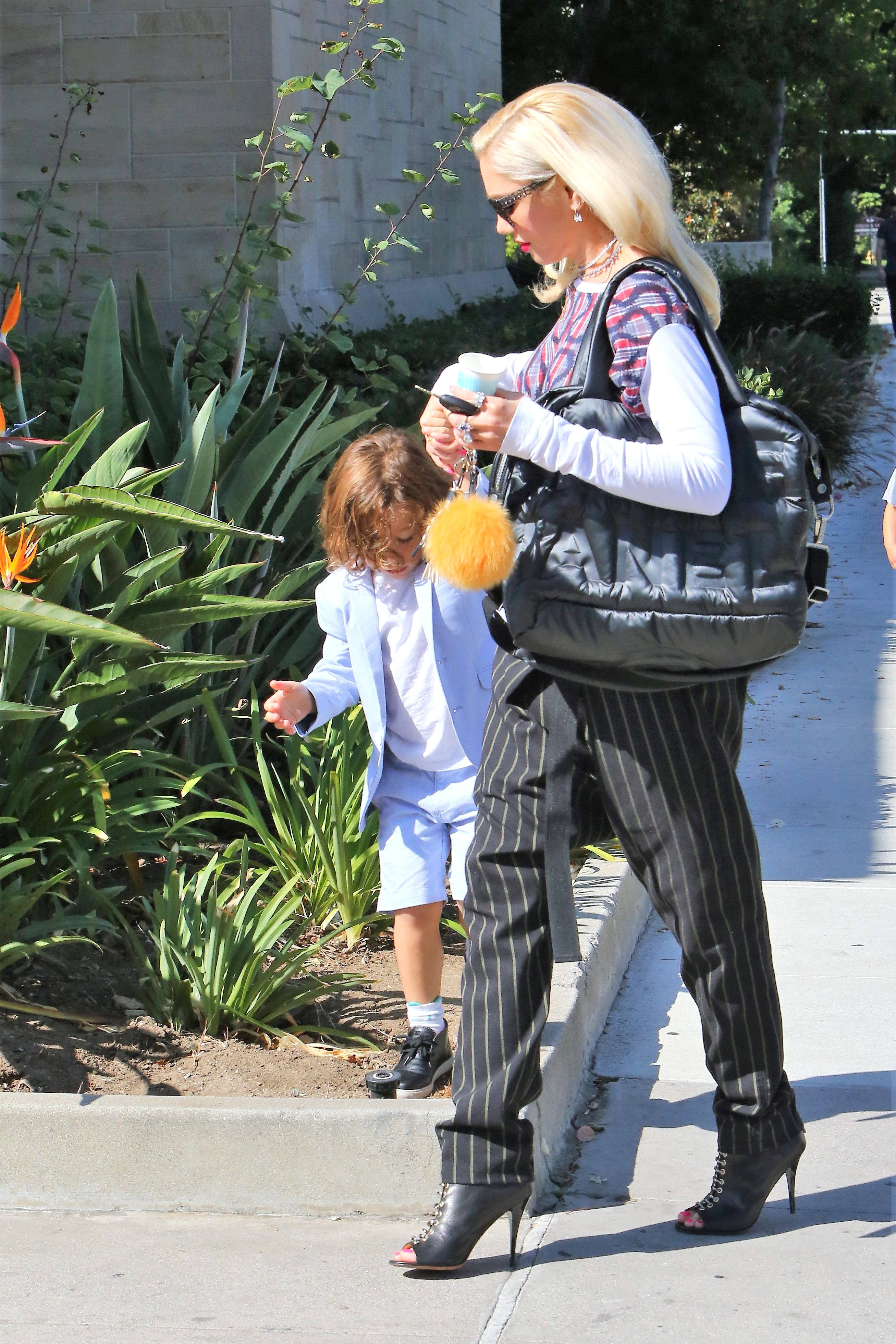 Gwen Stefani and her boys got up and out early for Sunday morning services at their family church in Los Angeles.  Platinum blonde Gwen looked stunning, in a colorful designer top over pin-striped slacks, with shades, on October 8, 2017  X17online.com