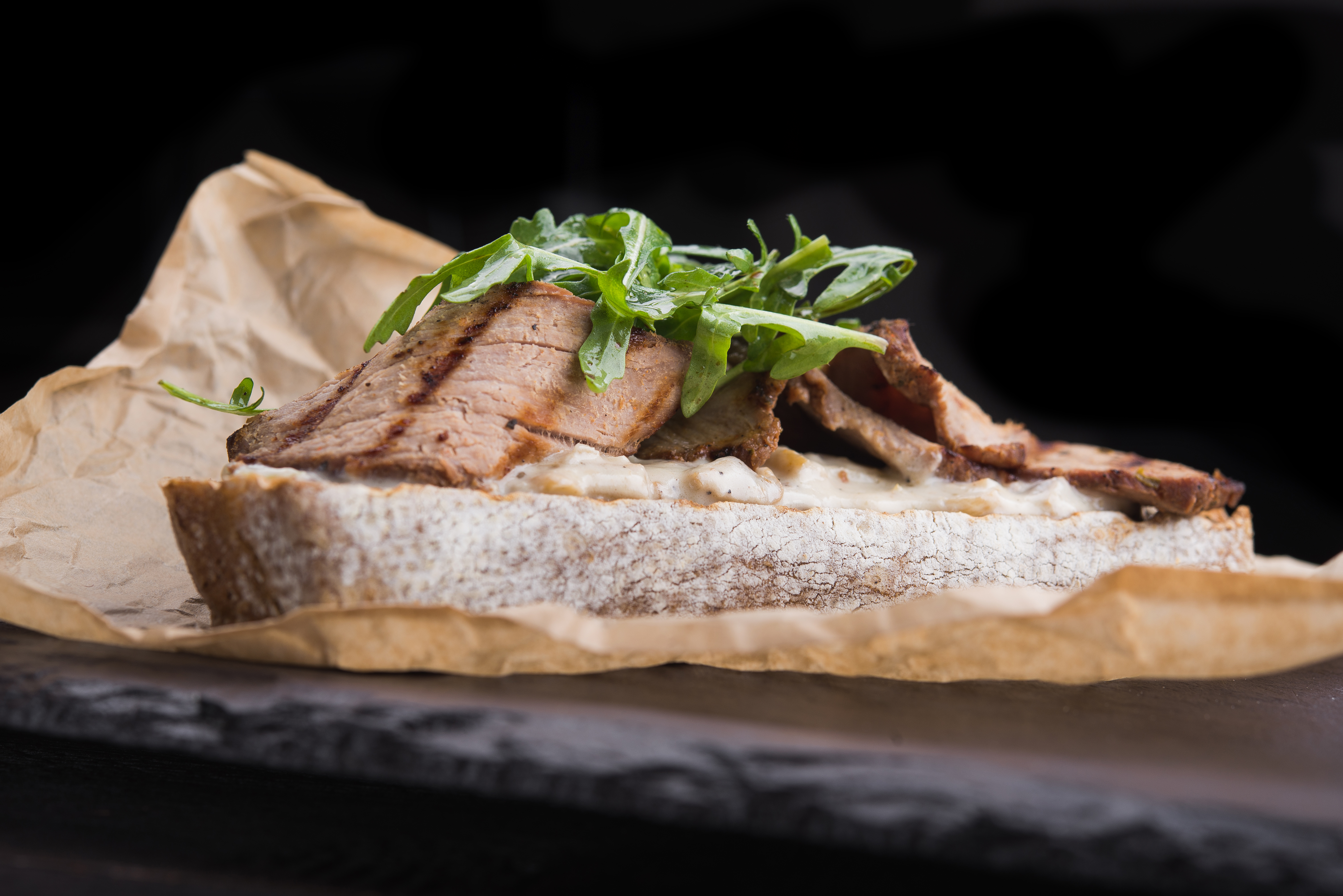 sandwich with mushroom sauce and beef on stone board