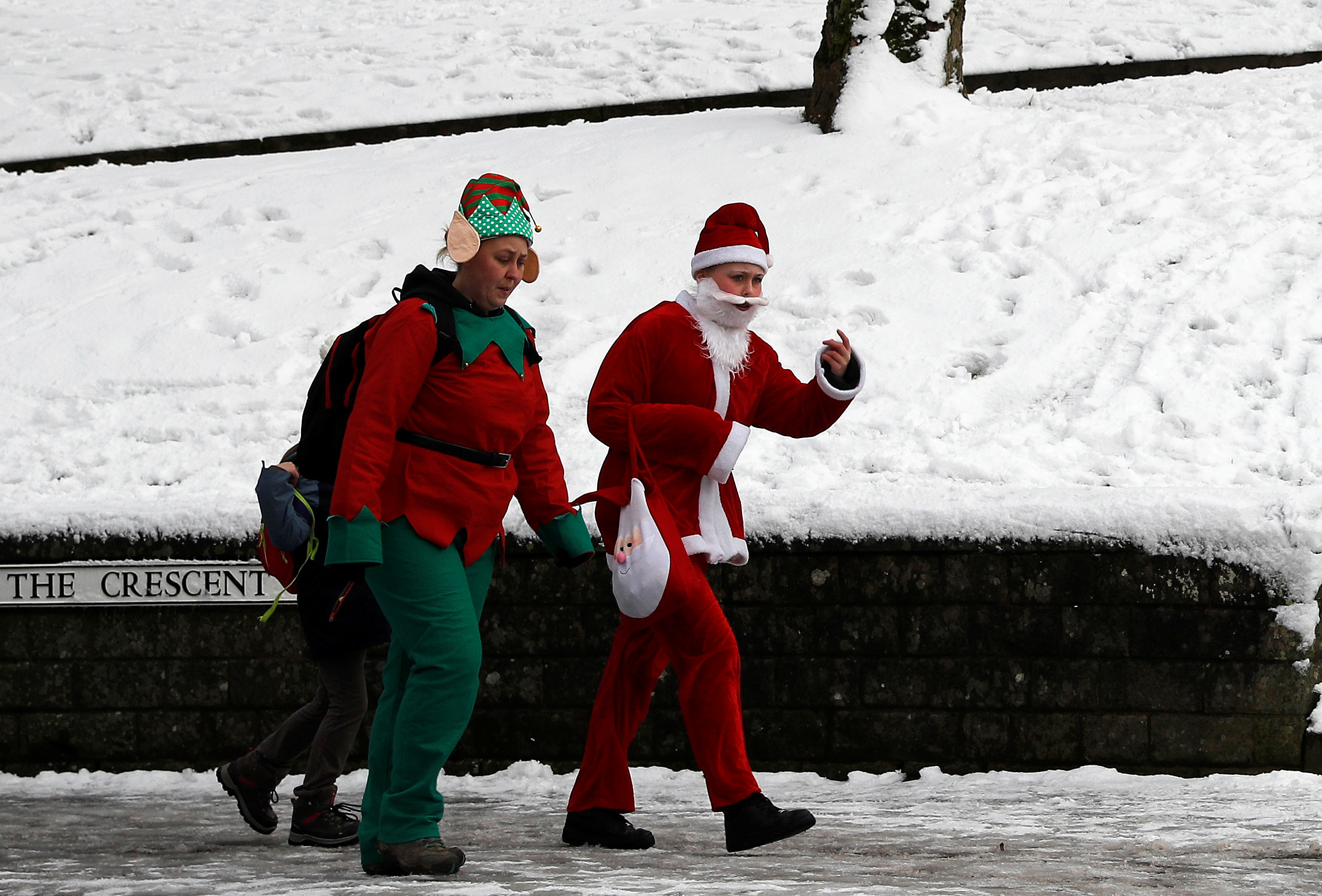 Women in festive fancy dress walk after a snow fall in Buxton, Britain December 9, 2017. Picture taken December 9, 2017. REUTERS/Darren Staples - RC170049A4D0