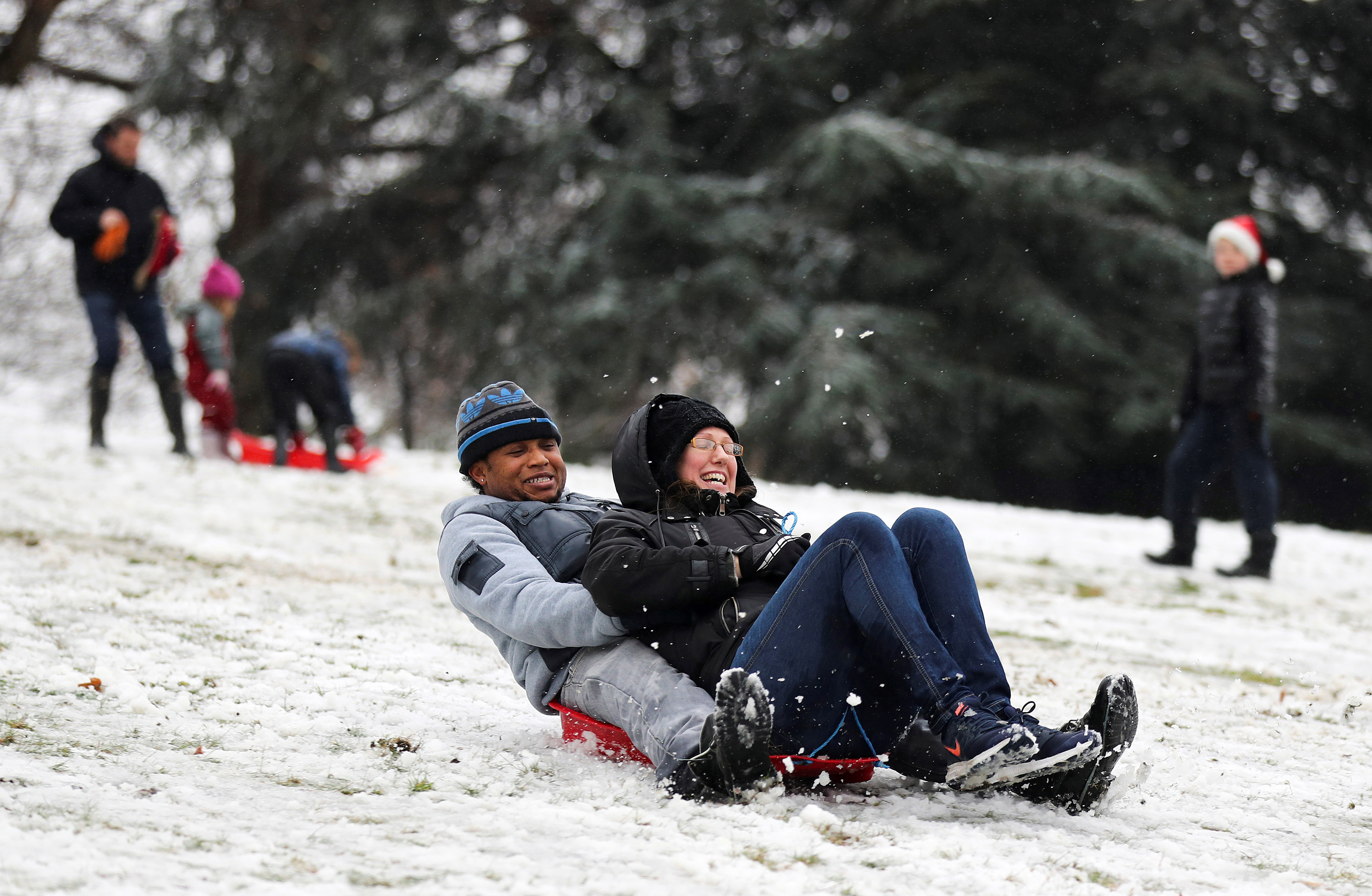 People sled down a hill in the snow in Greenwich Park, London, Britain December 10, 2017. REUTERS/Simon Dawson - RC1CC6D95220
