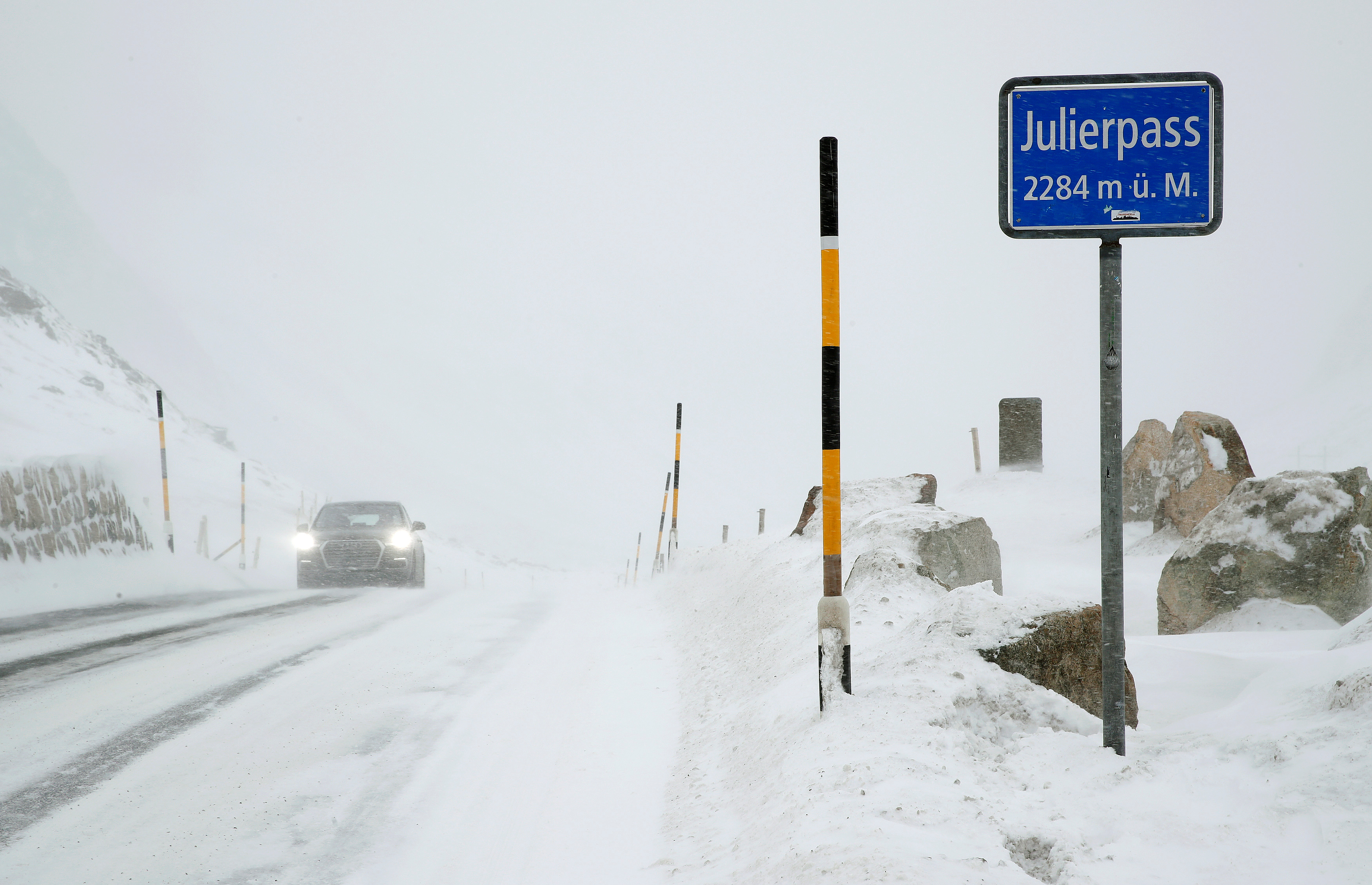 A car drives on the snow-covered road over the summit of the Julierpass mountainpass (2,284 m/7,493 ft above sea level) in the Canton of Grisons, Switzerland December 10, 2017. REUTERS/Arnd Wiegmann - RC1A78236960