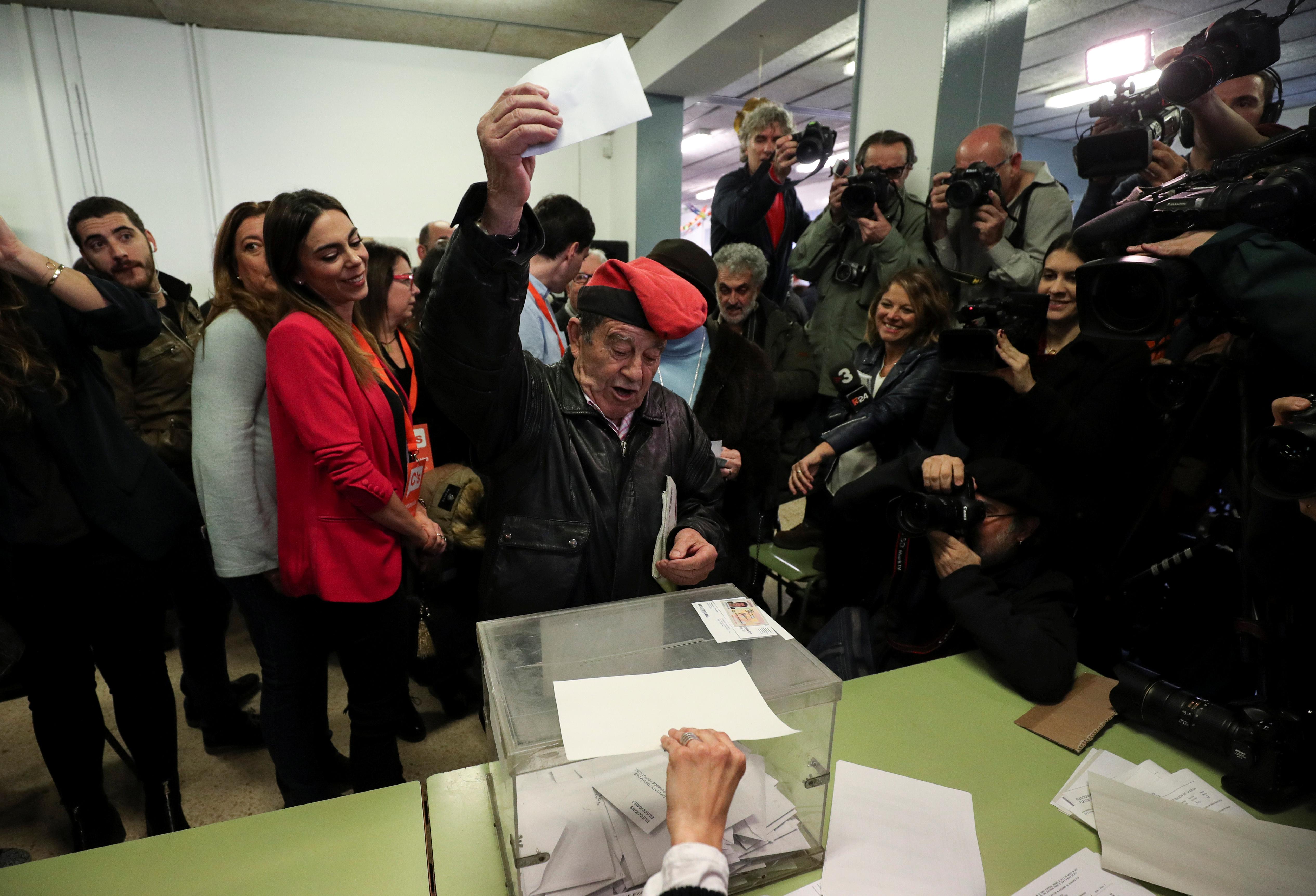 """Muškarac nosi """"barretinu"""", tradicionalnu katalonsku kapu, dok ubacuje svoj glas na jednom od biračkih mjesta u Barceloni, Španjolska, 21.12.2017."""