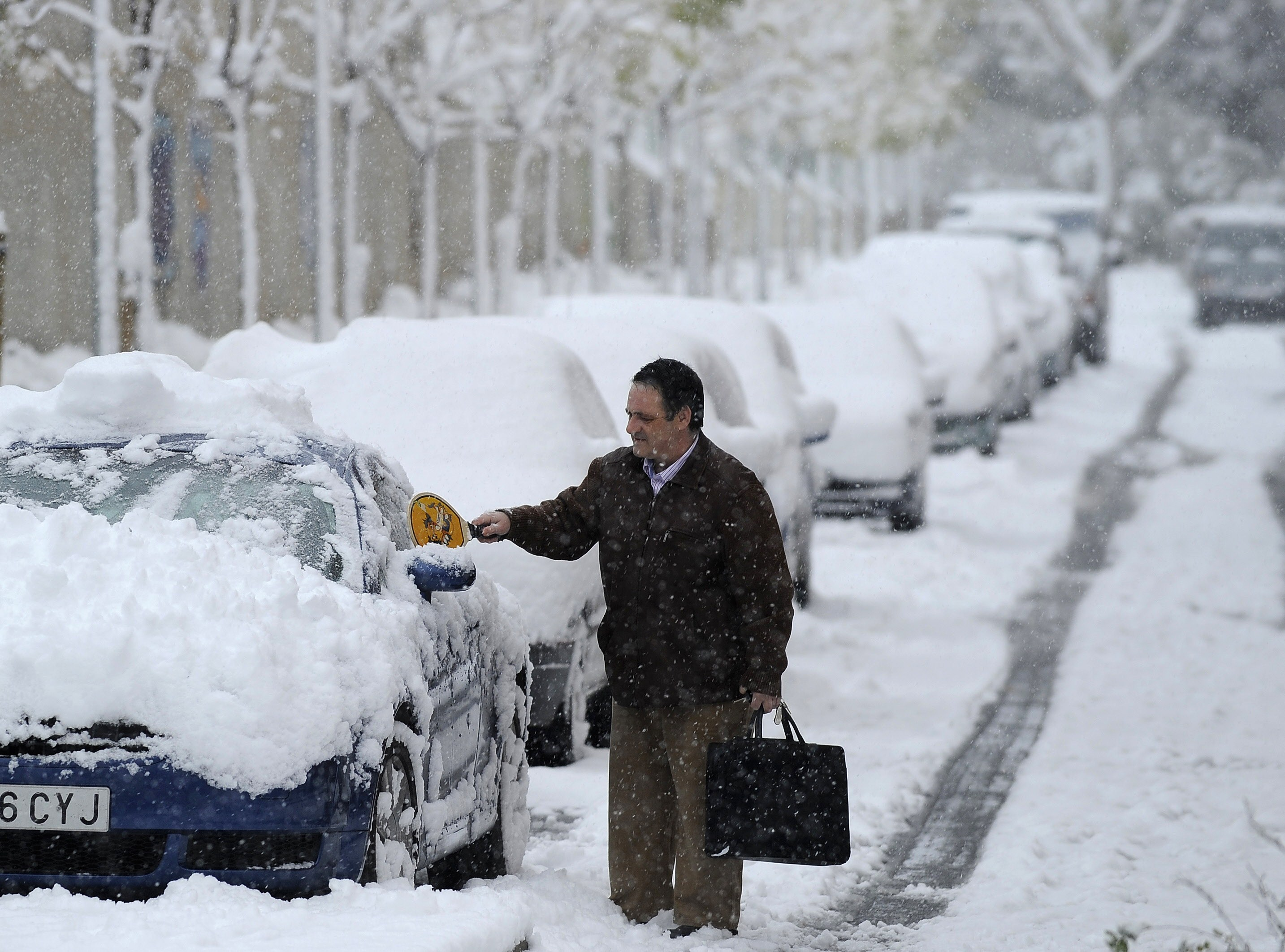 A man removes snow from his car, on December 14, 2009 in Aranjuez, near Madrid, during the first snow fall of the season. AFP PHOTO/Pedro ARMESTRE