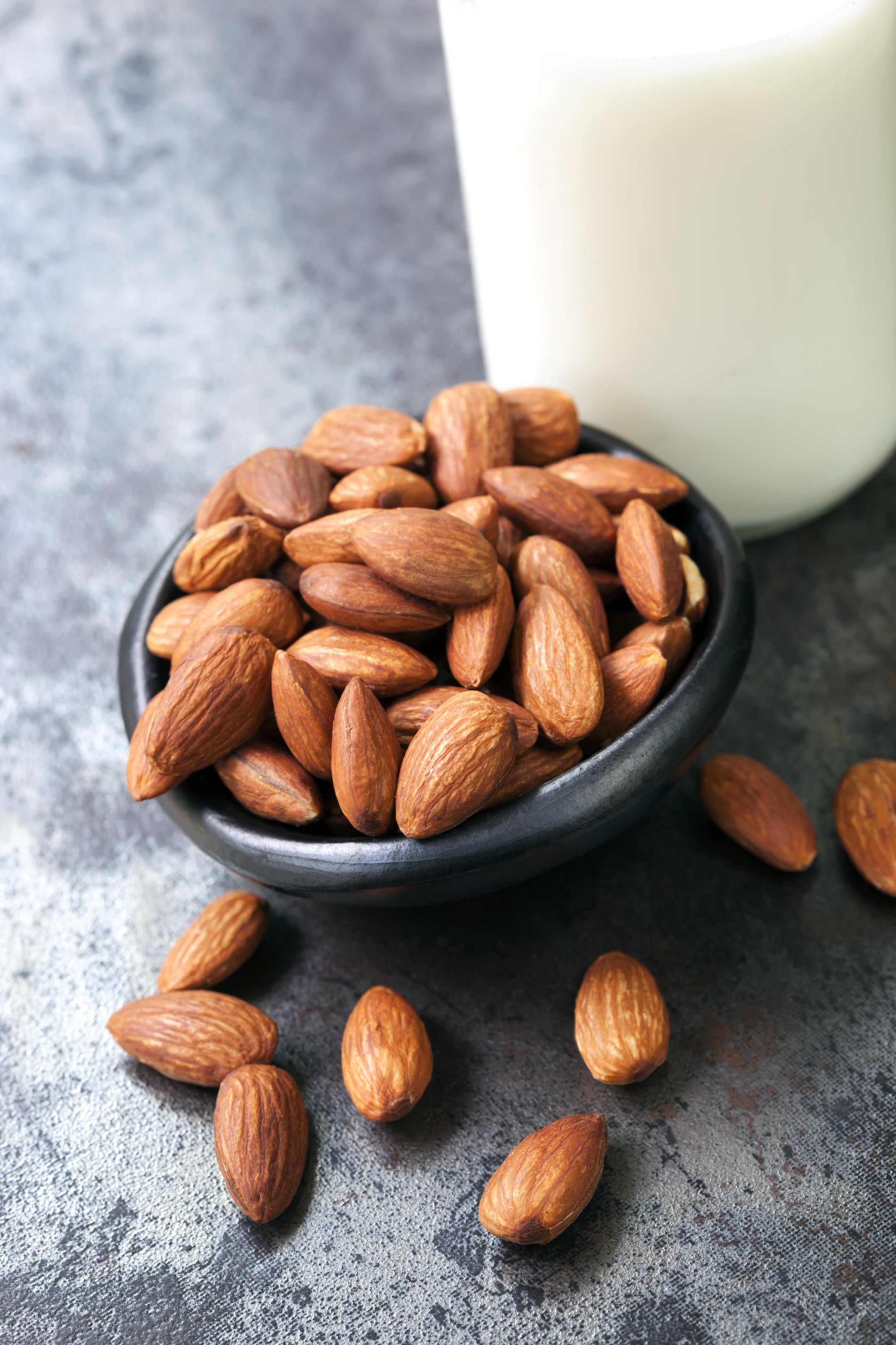 Almonds with almond milk, on dark slate background.