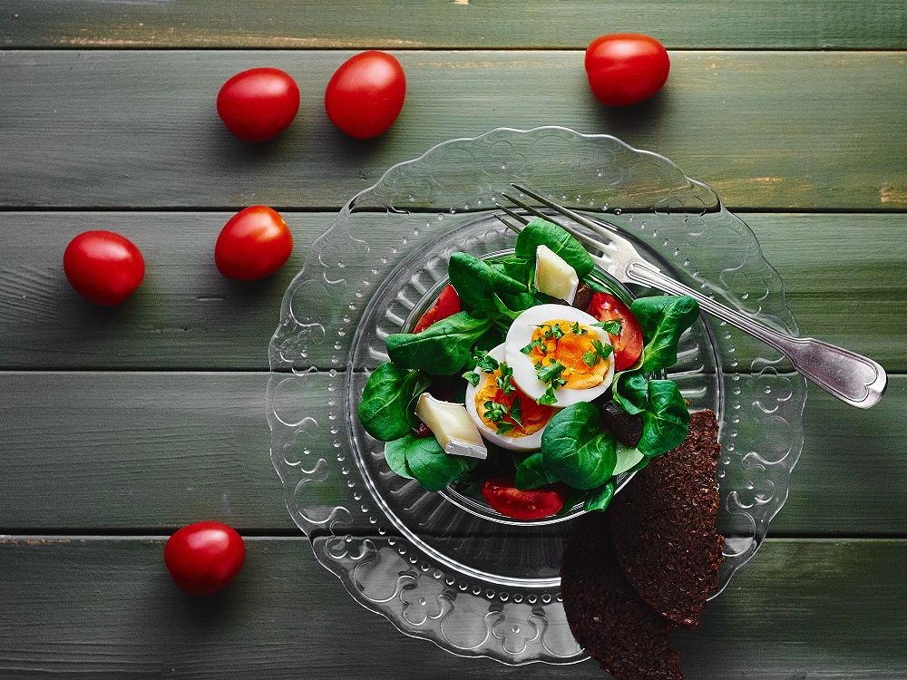 Green corn salad in a small bowl with egg and tomatoes