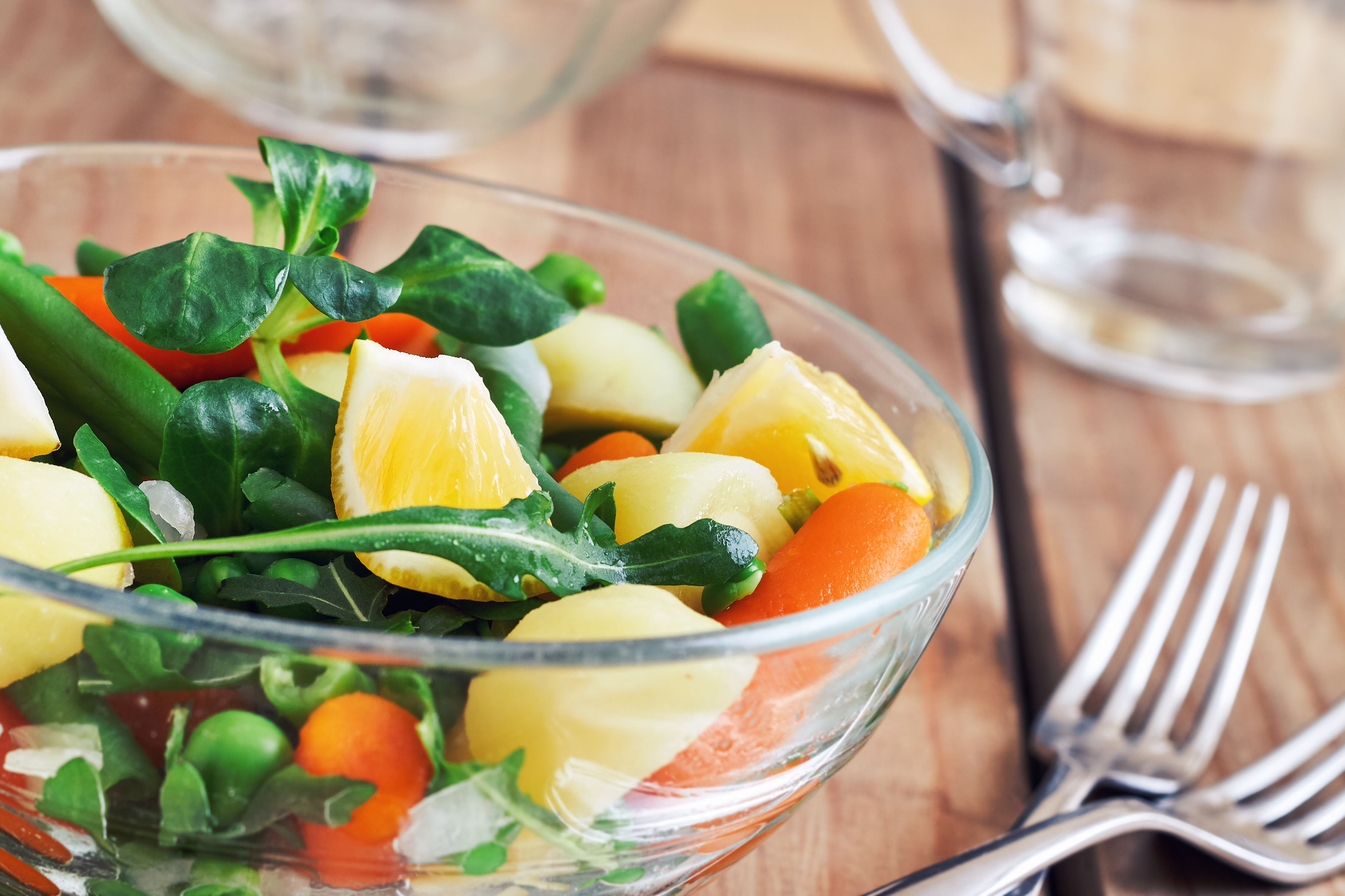 Salad with baby carrots, peas, onions and potatoes in glass bowl on wooden background