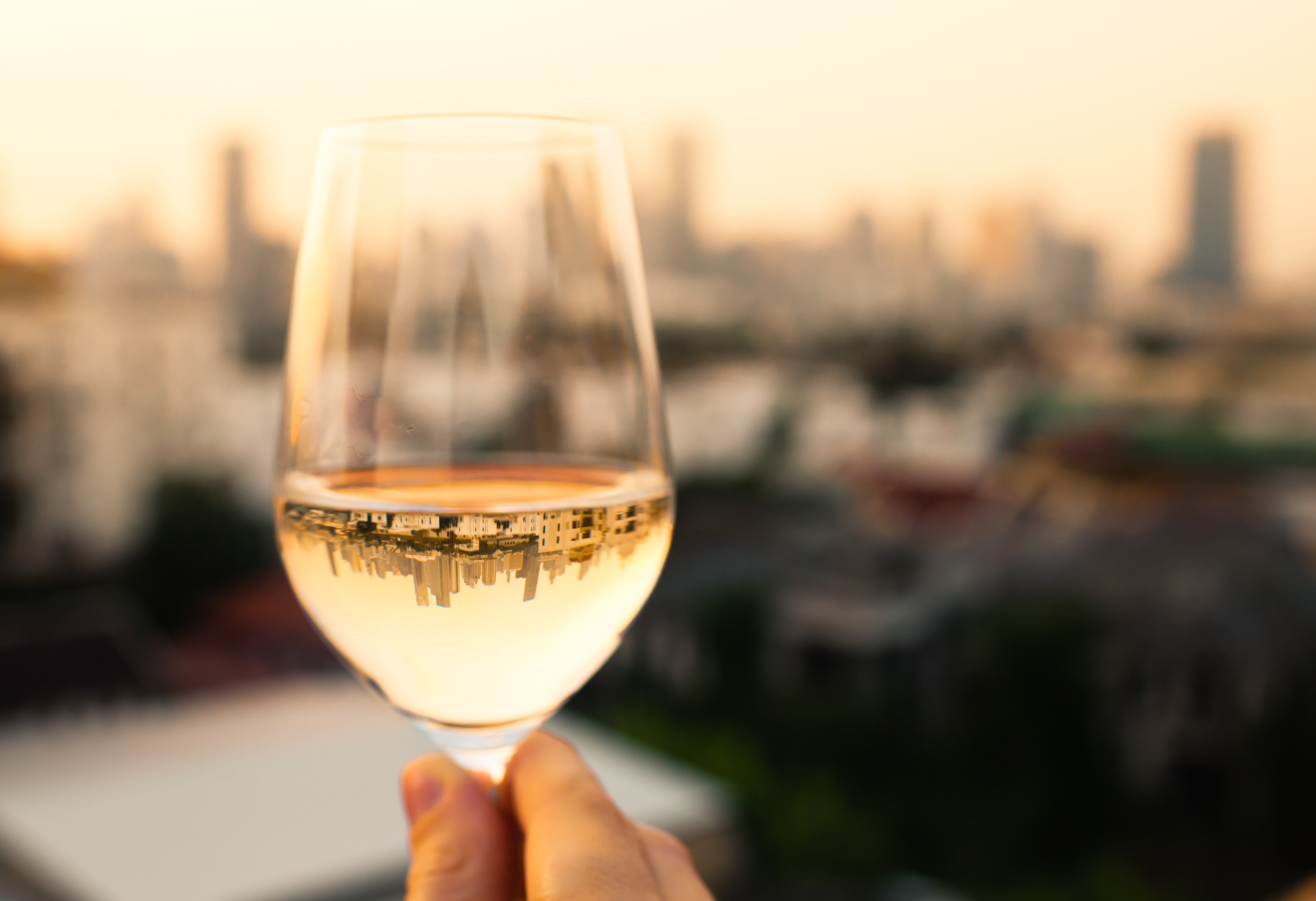 Woman enjoying glass of wine in the city.