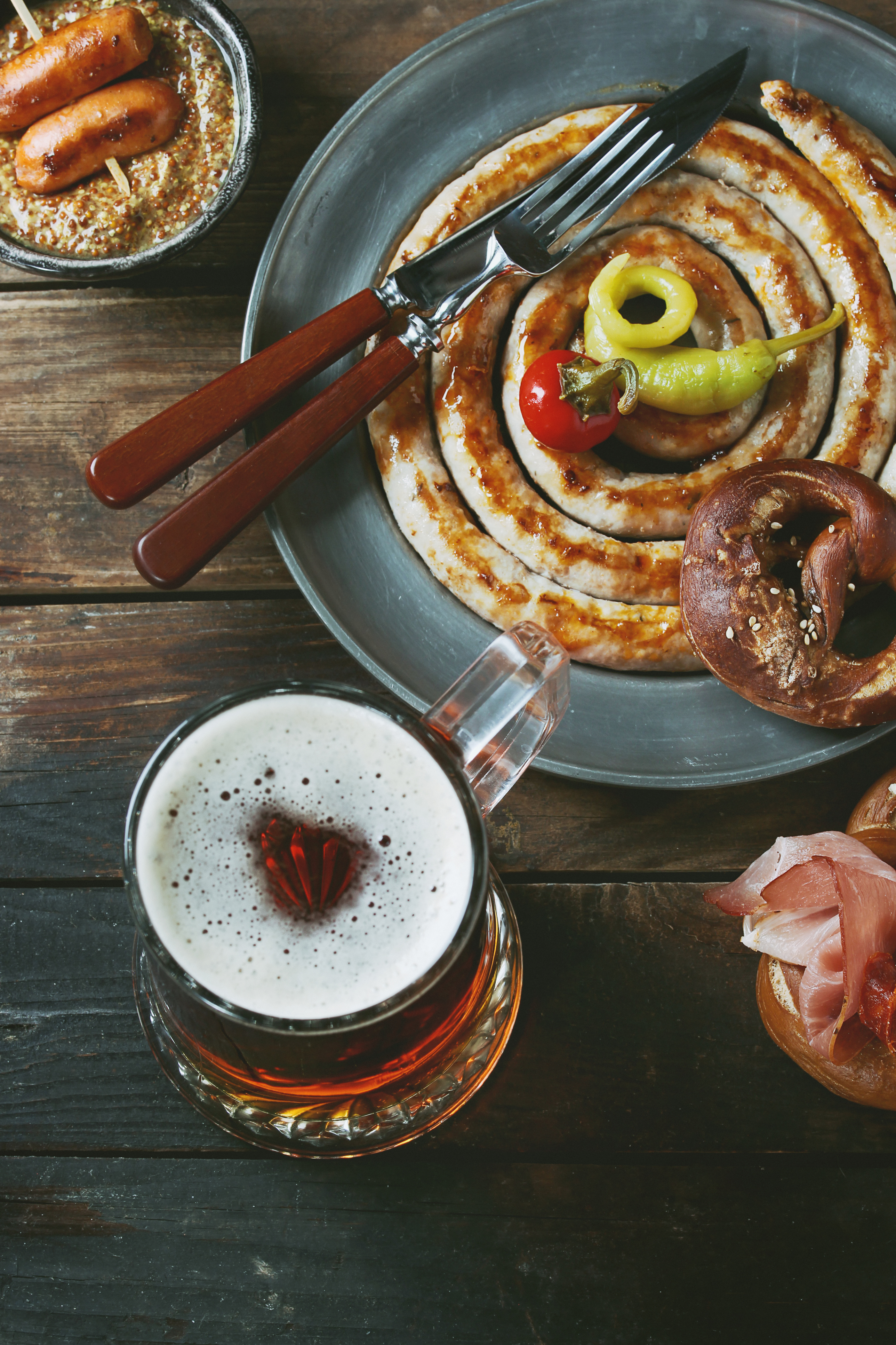Big spiral fried sausage, meat snacks wienerwurst, ham, marinated chili peppers served in salted pretzels and plate with glass of lager beer and mustard over dark wooden background. Top view