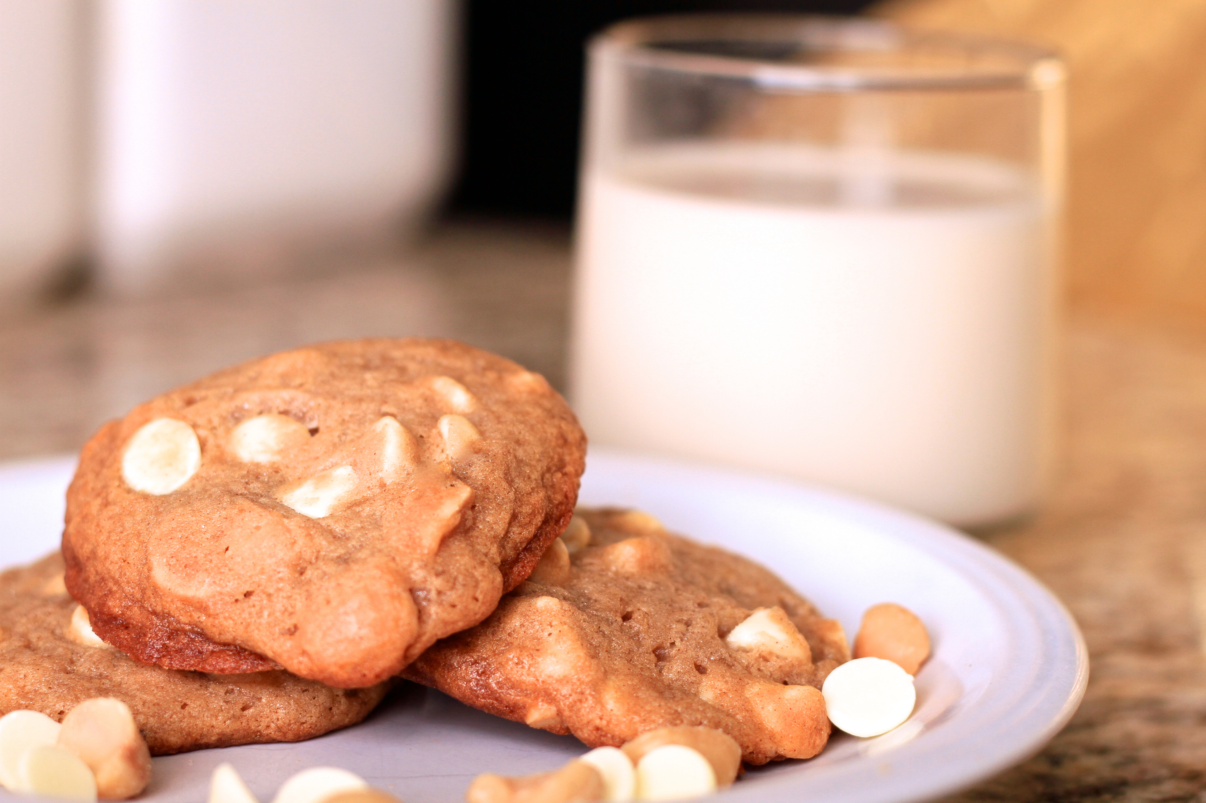 A plate of home made white chocolate and macadamia nut cookies are garnished with additional nuts and white chocolate chips and served with almond milk, These cookies are completely vegan and the milk is almond milk.