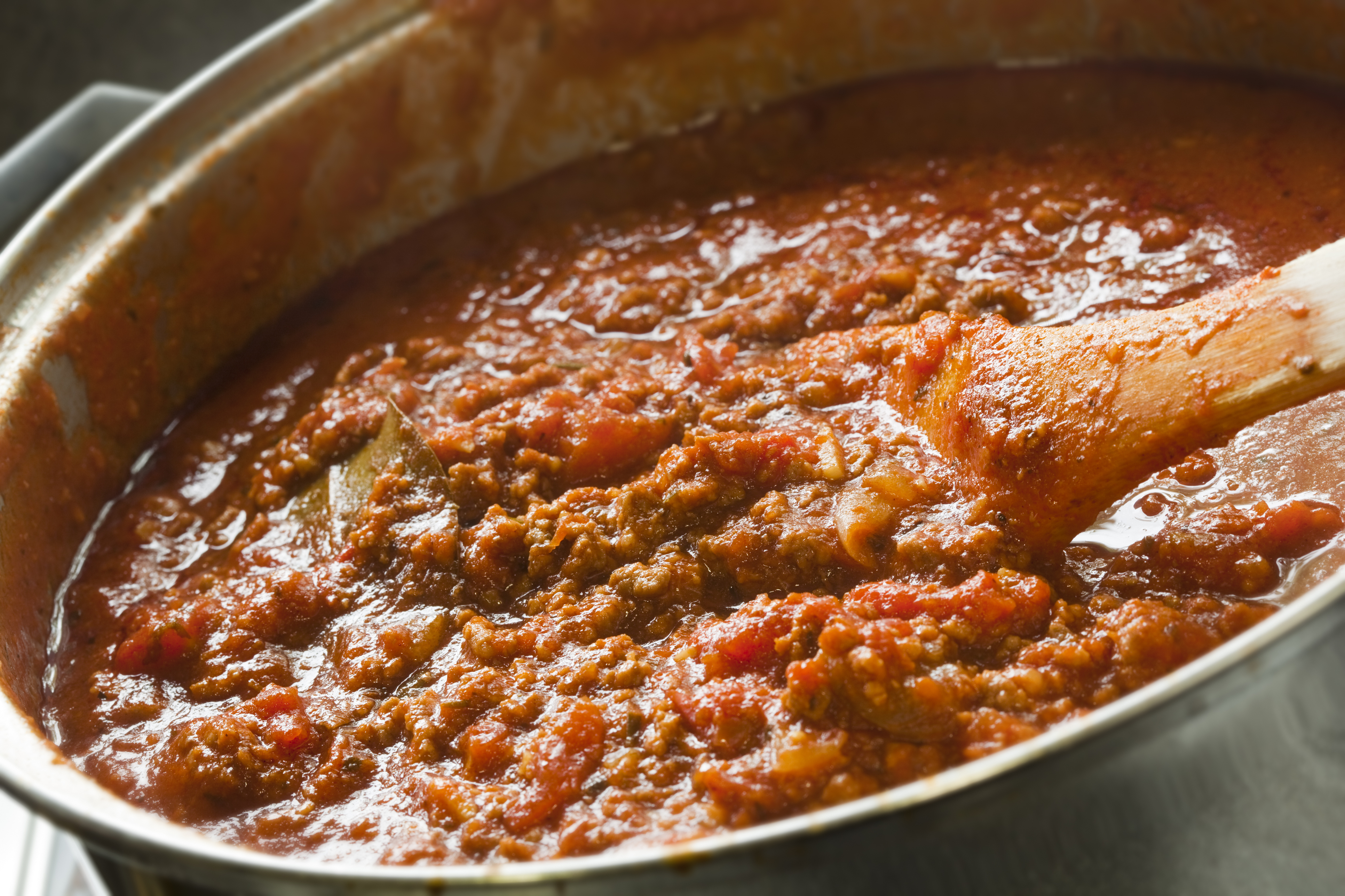 Rich Bolognese sauce cooking in a saucepan, with wooden spoon, ready for your pasta dish.  More beef images: