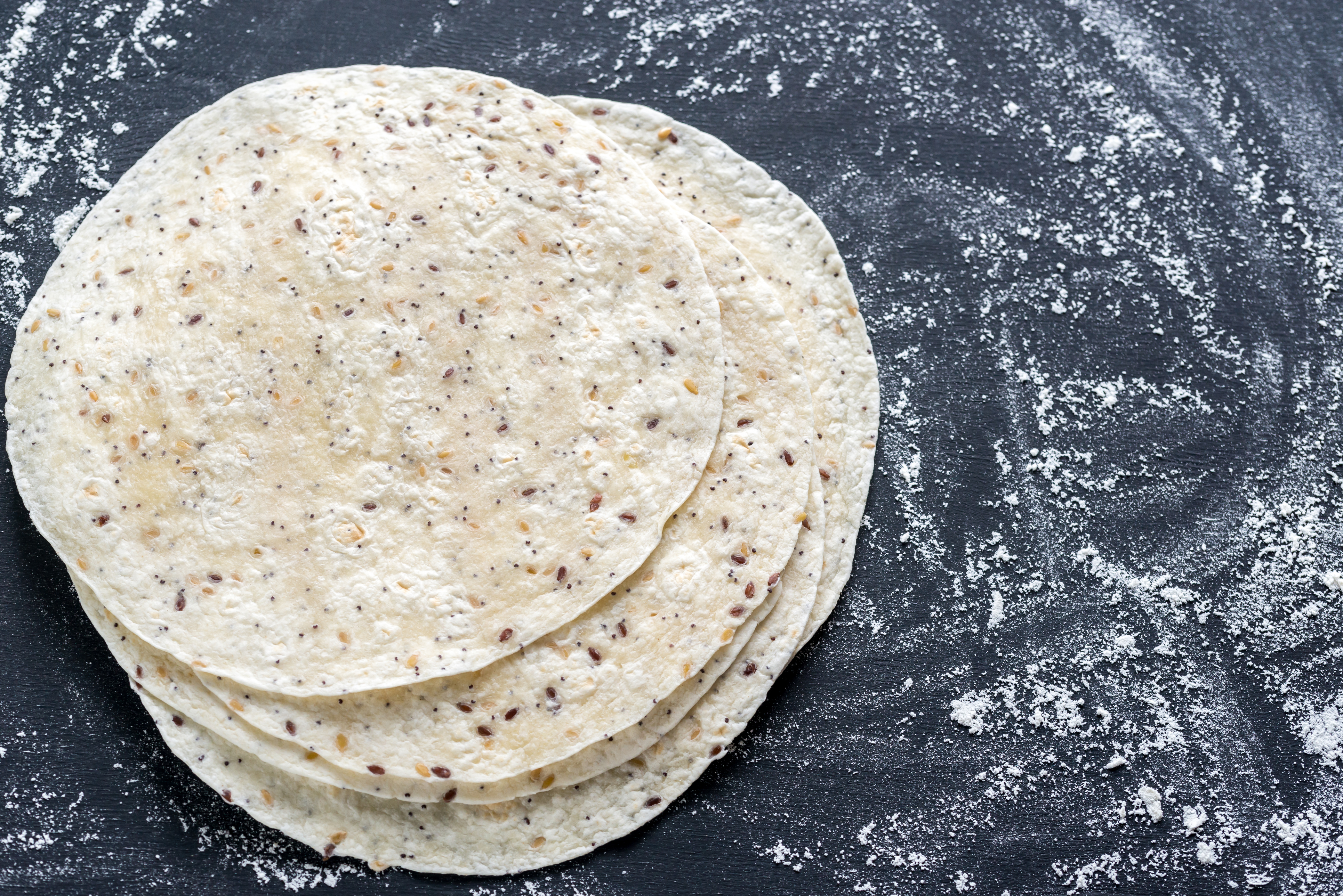 Stack of tortillas on a black surface