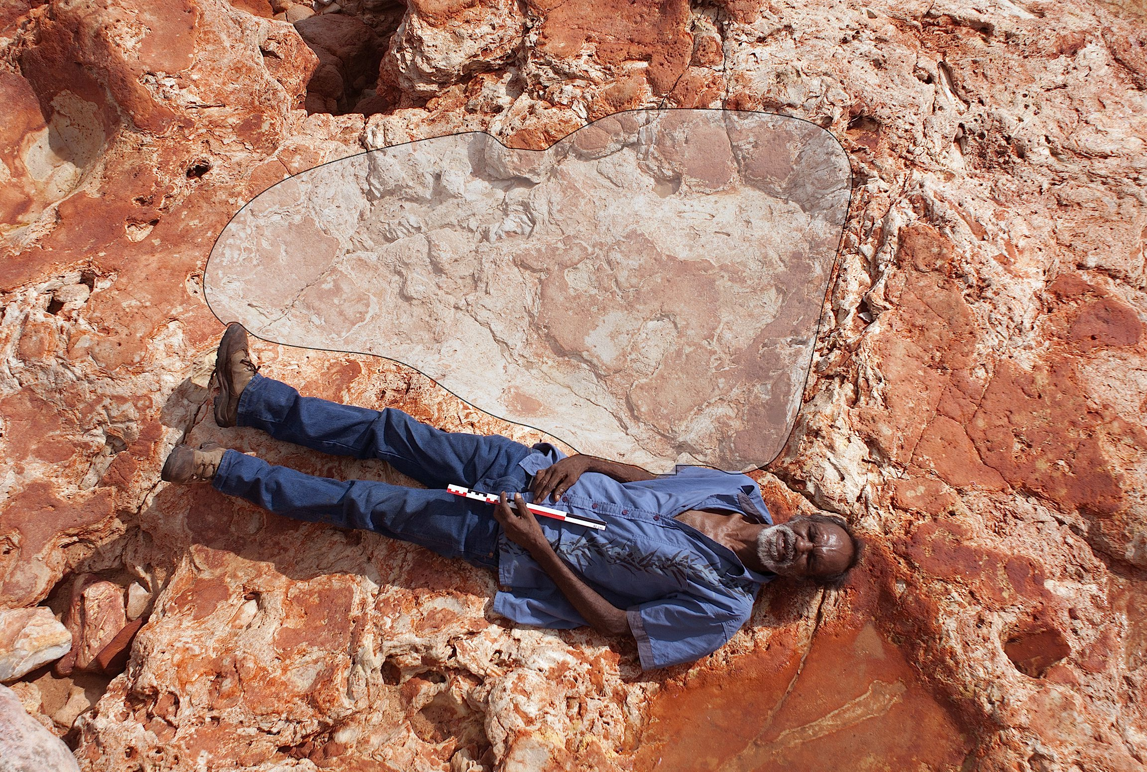 Aboridžinski starješina i šef prava naroda Goolarabooloo Richard Hunter leži pored 175cm otiska stopala sauropoda