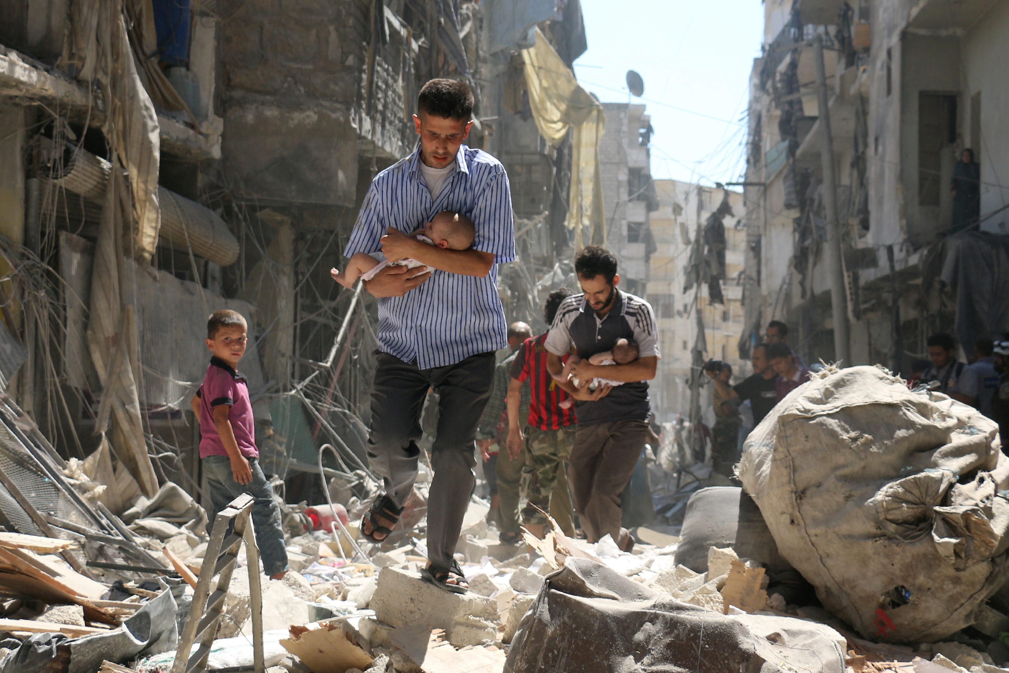 Syrian men carrying babies make their way through the rubble of destroyed buildings following a reported airstrike on the rebel-held Salihin neighborhood of Aleppo on 11 September 2016. Airstrikes have killed dozens in rebel-held parts of Syria as the opposition considers whether to join a US-Russia truce deal due to take effect on 12 September. Ameer Alhalbi, Agence France-Presse/Courtesy of World Press Photo Foundation/Handout via REUTERS   THIS IMAGE HAS BEEN SUPPLIED BY A THIRD PARTY. FOR EDITORIAL USE ON WORLD PRESS PHOTO ONLY. NO RESALES. NO CROPPING