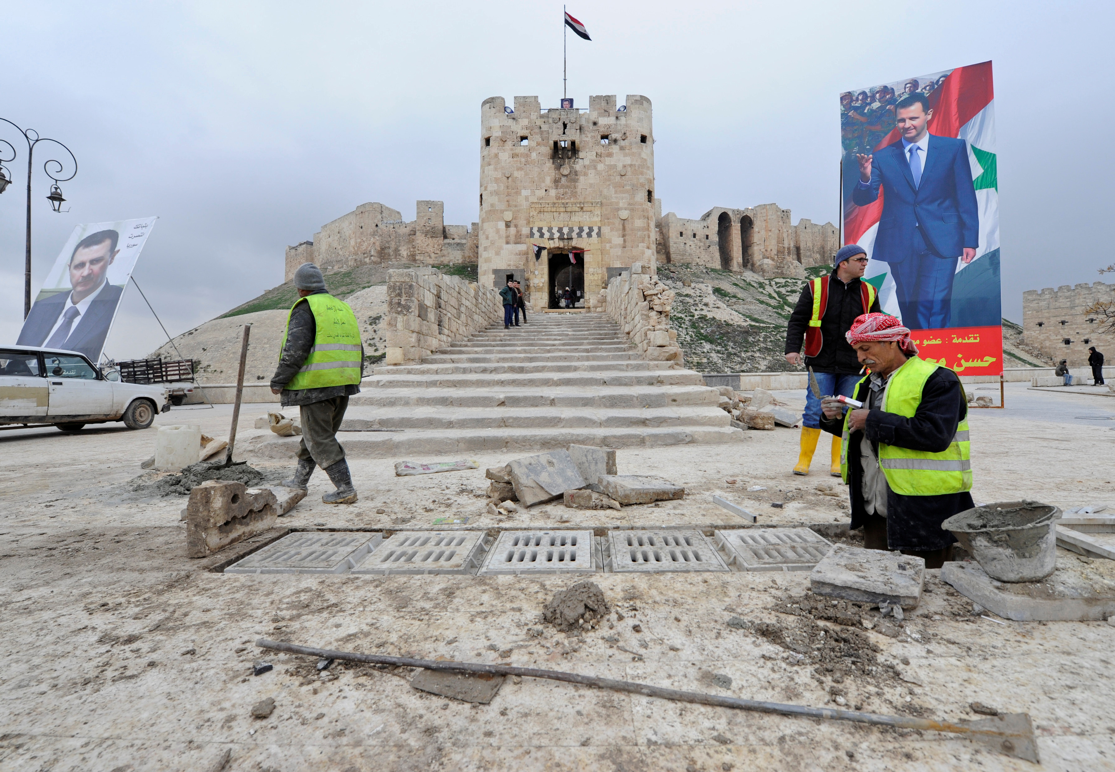 Workers repair the damage in front of Aleppo's historic citadel, as posters depicting Syria's President Bashar al-Assad are erected in the Old City of Aleppo, Syria January 31, 2017. REUTERS/Omar Sanadiki - RTX2Z0RF