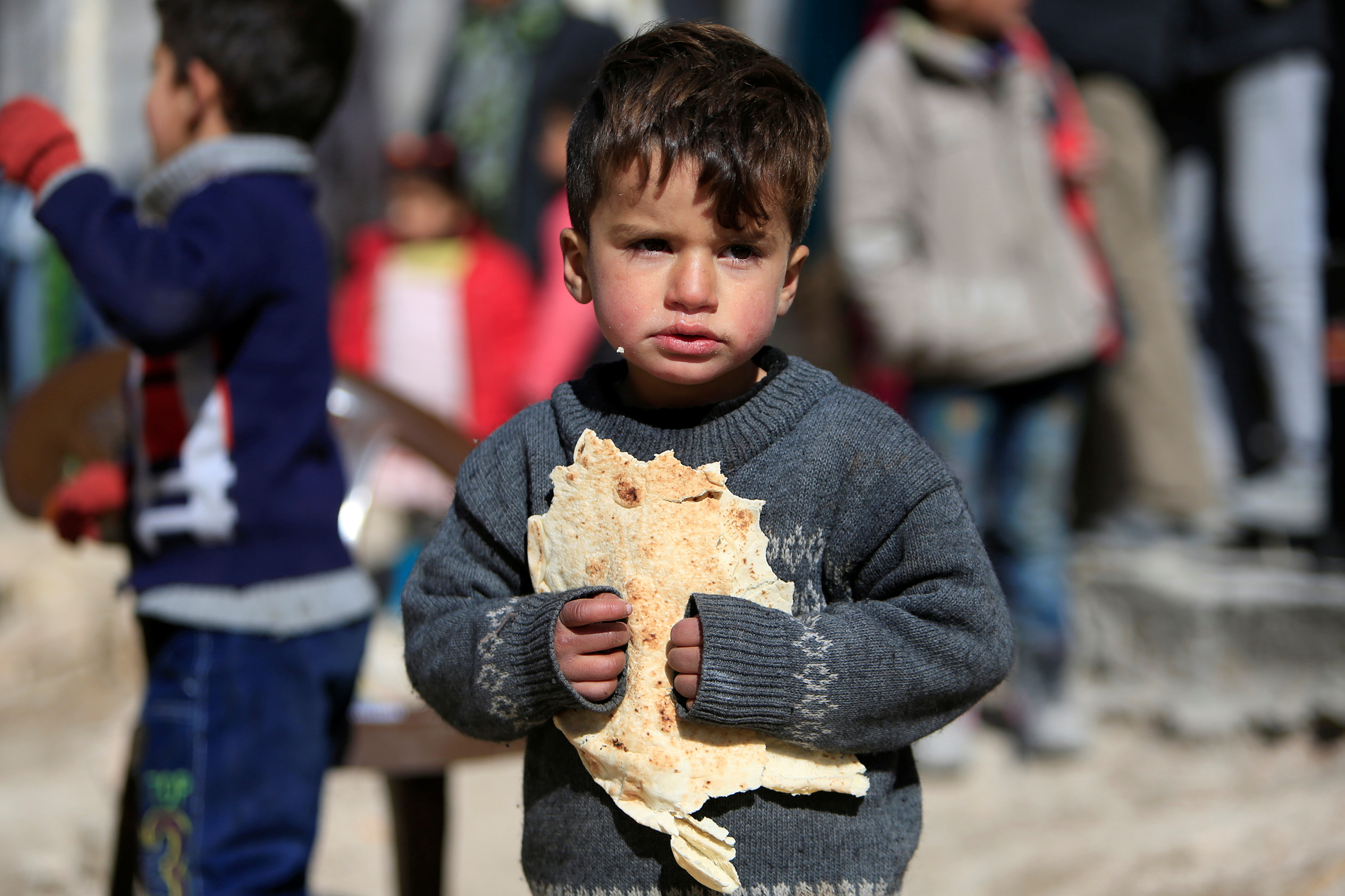A displaced boy carries bread at a shelter in Jibreen, on the outskirts of Aleppo, Syria February 1, 2017. REUTERS/Ali Hashisho - RTX2Z7ID